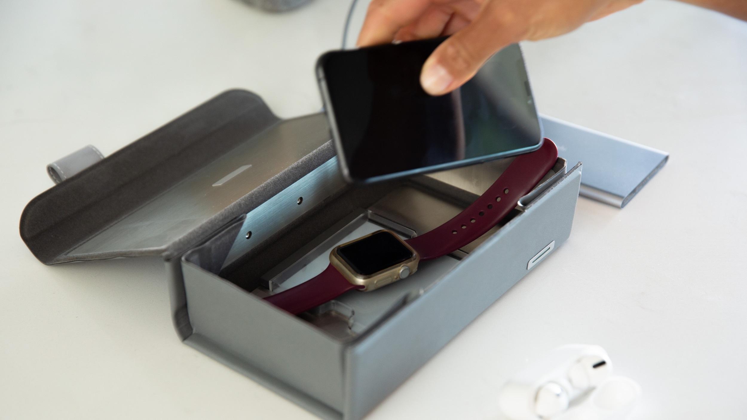 Placing a smartphone into a Moshi Deep Purple UV sanitizer