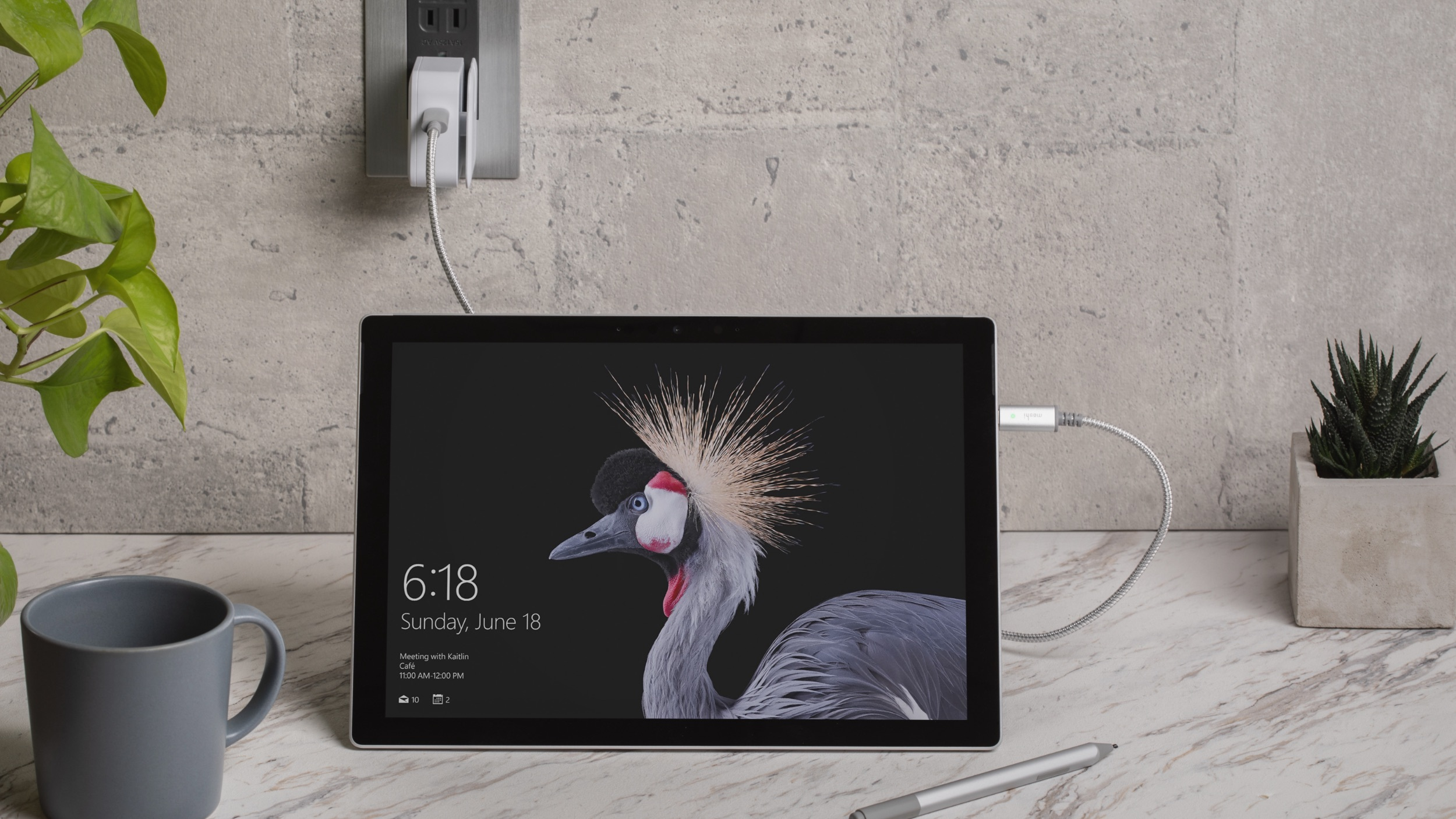 A Surface Go with type cover removed standing up on a marble benchtop. The lock screen is visible