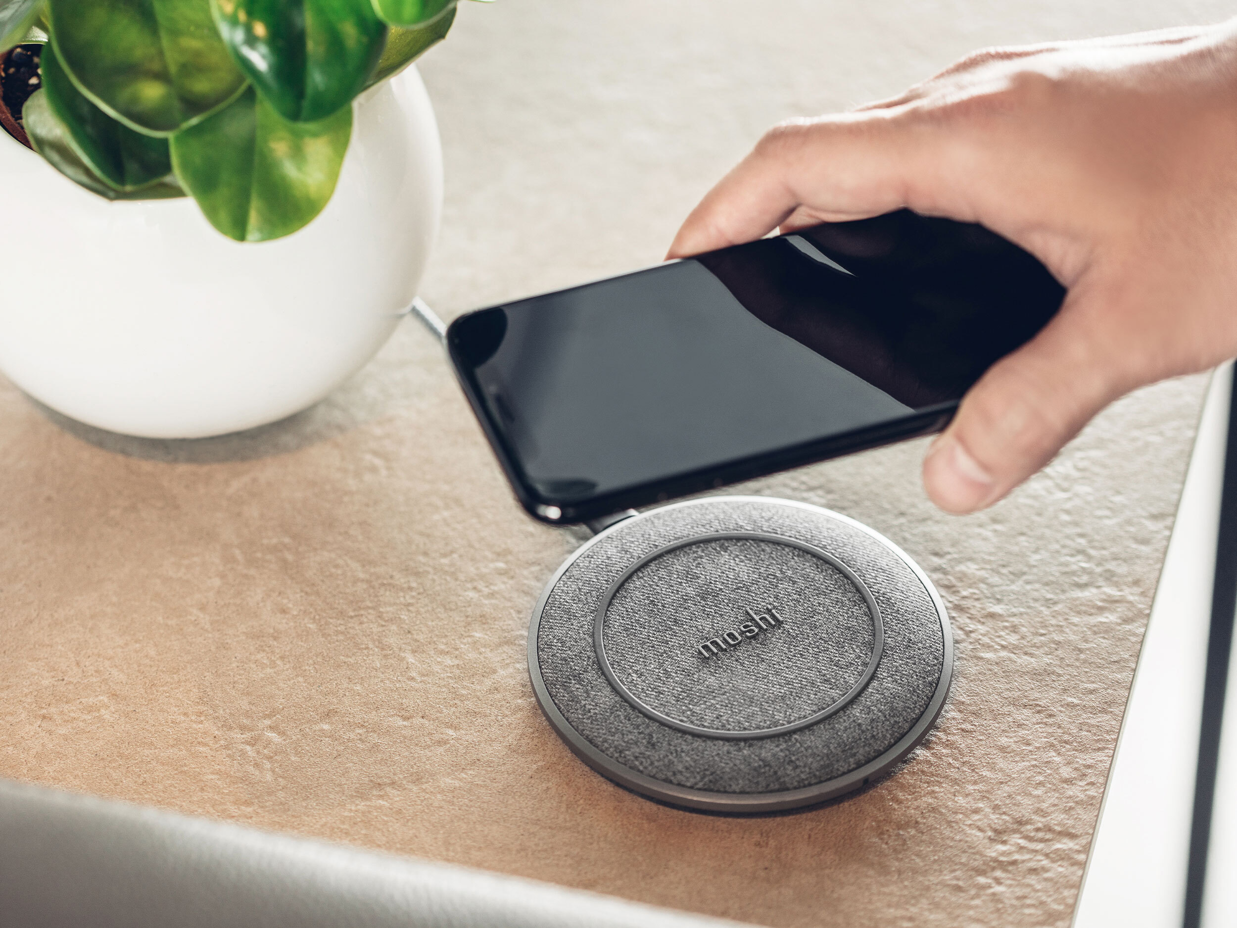 A hand placing a smartphone down on a Moshi Otto Q wireless charging pad