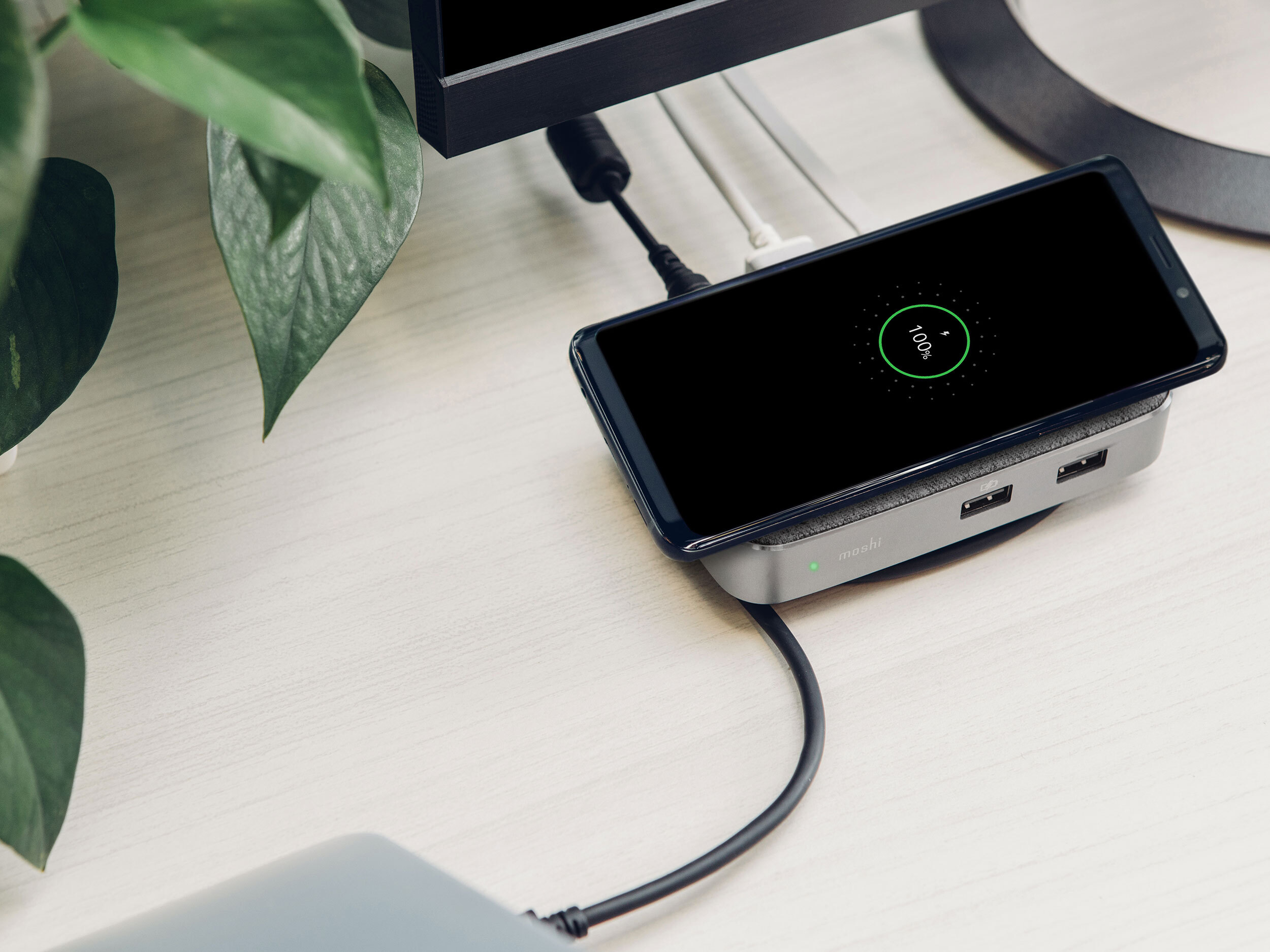 A smartphone charging wirelessly on top of a Moshi Symbus Q wireless charger on a desk