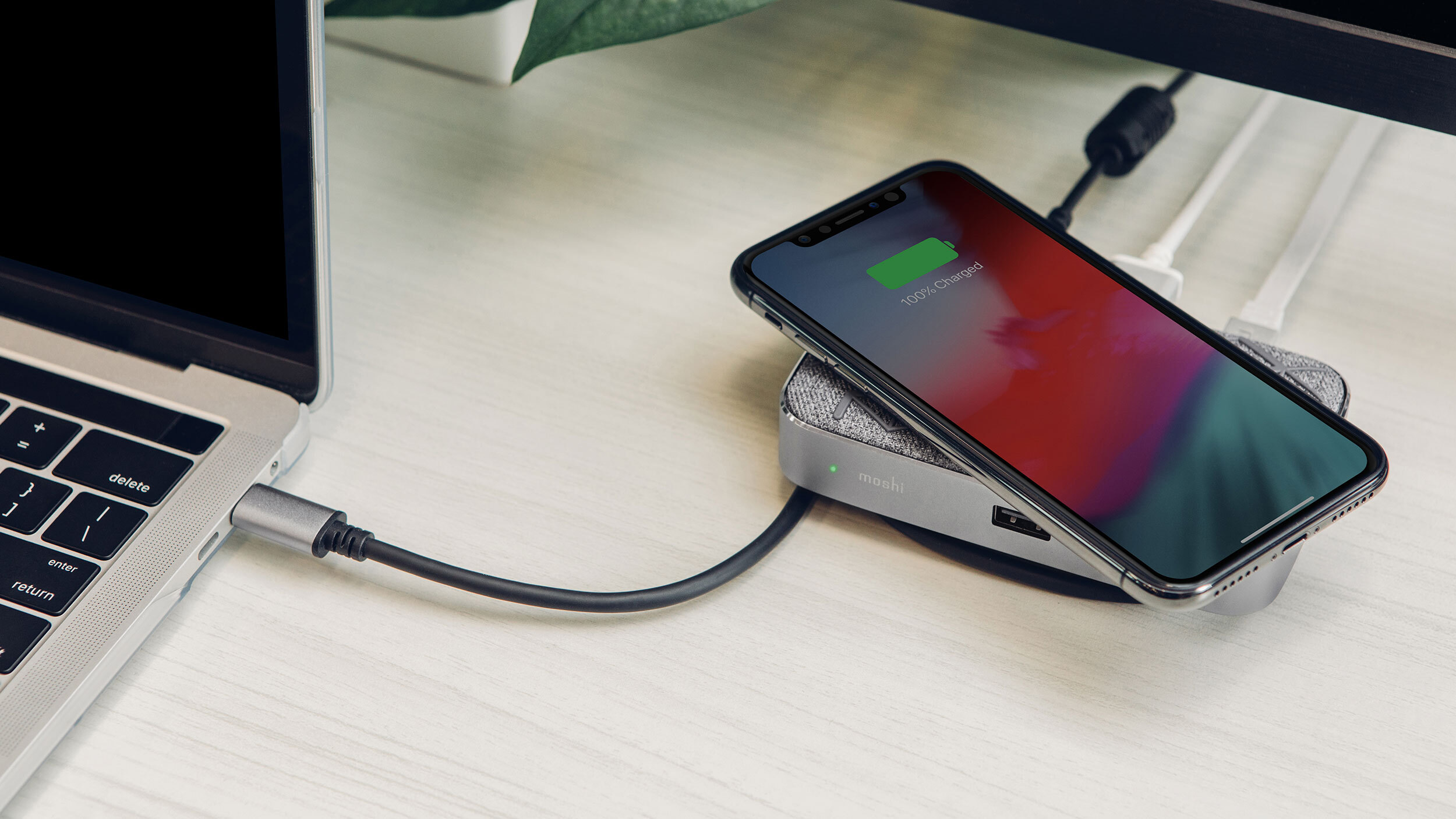 A smartphone charging on top of a Moshi Symbus Q hub which is connected to a laptop