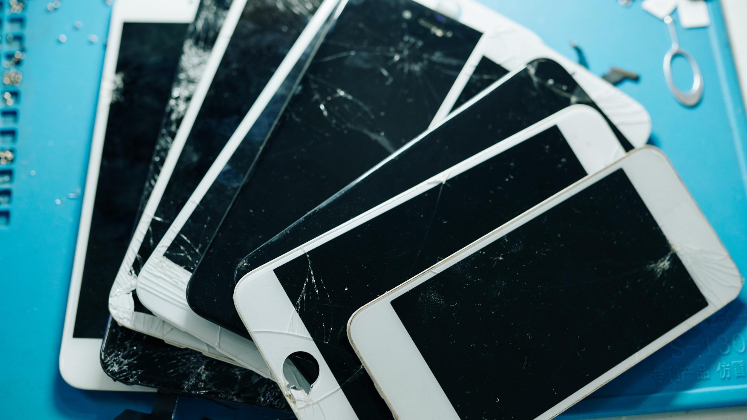 several smartphones with broken or cracked screens