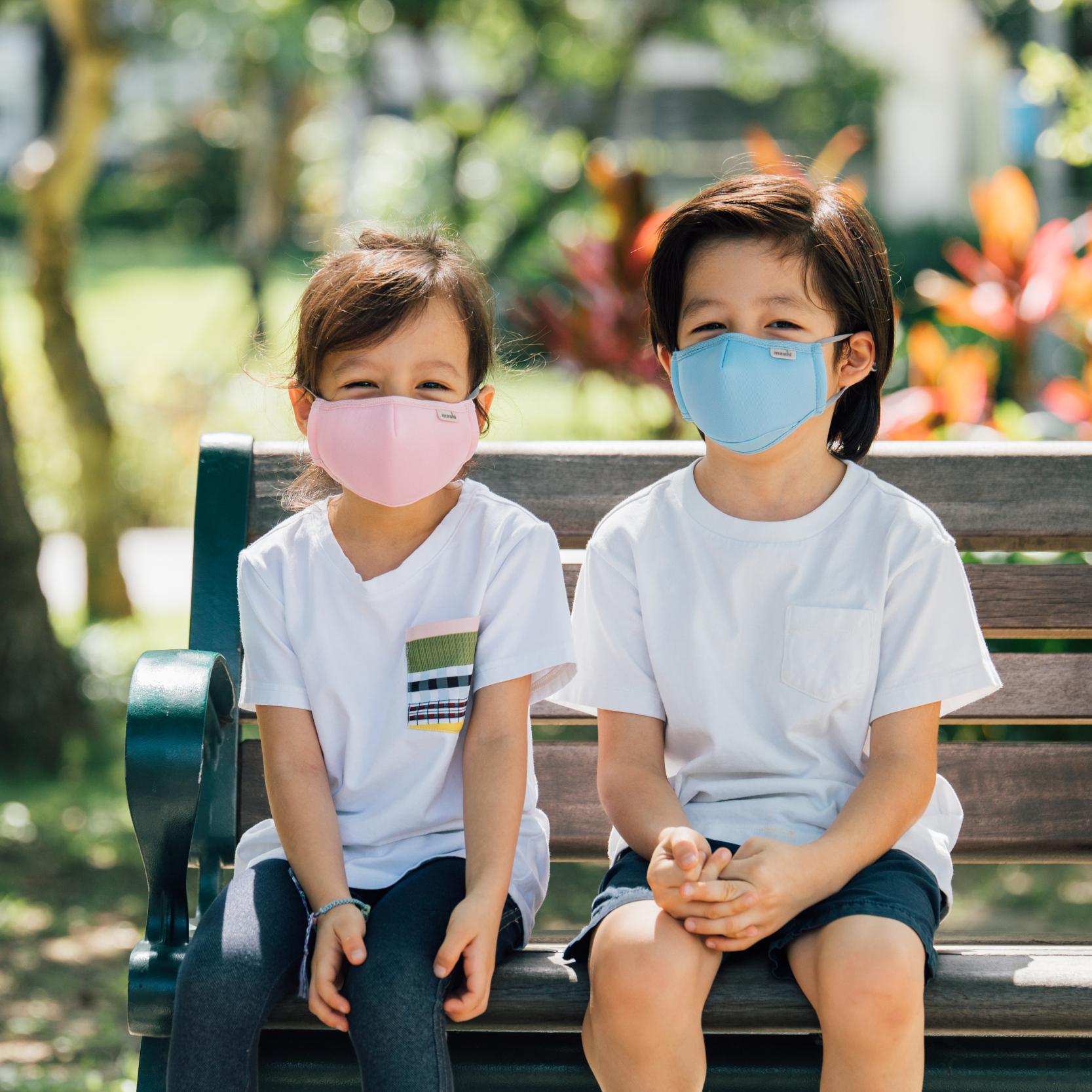 Two children sitting on a park bench wearing Moshi OmniGuard Kids masks