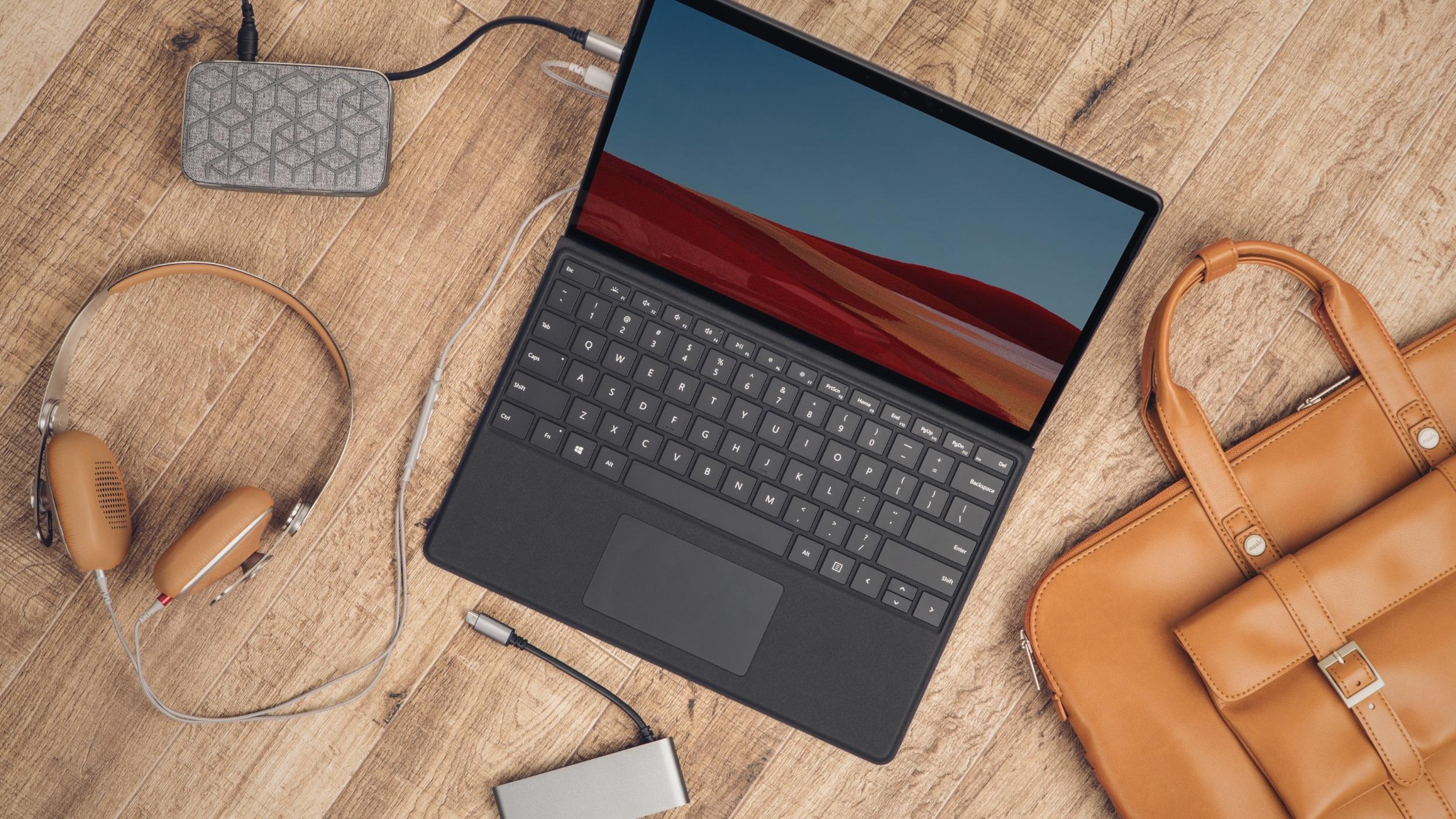 A Surface Pro device surrounded by compatible Moshi products; Avanti C headphones, Symbus Q USB-C hub, Symbus Mini 7-in-1 hub, Treya briefcase