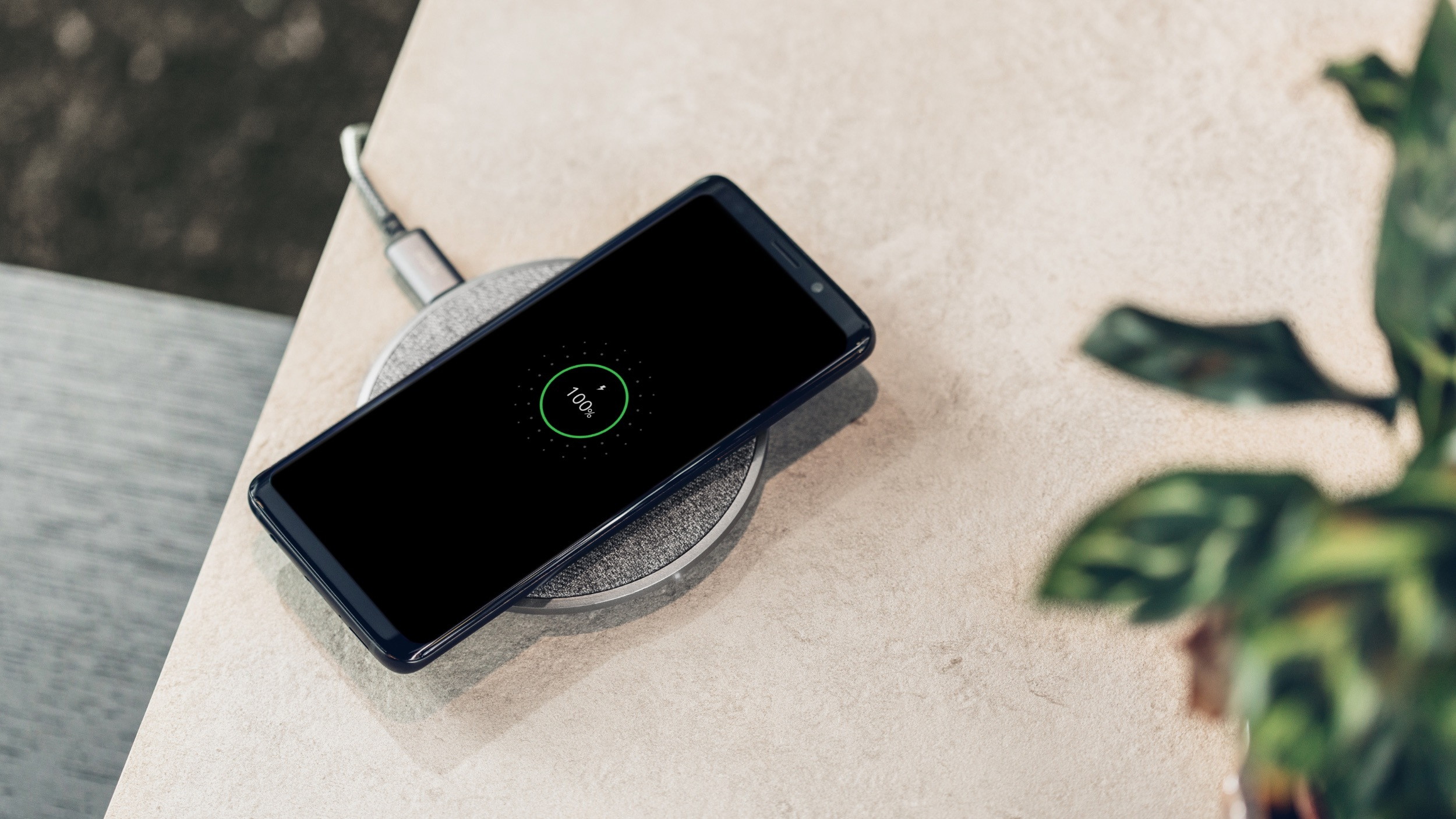 close-up view of a phone charging wirelessly with the screen showing 100% charged