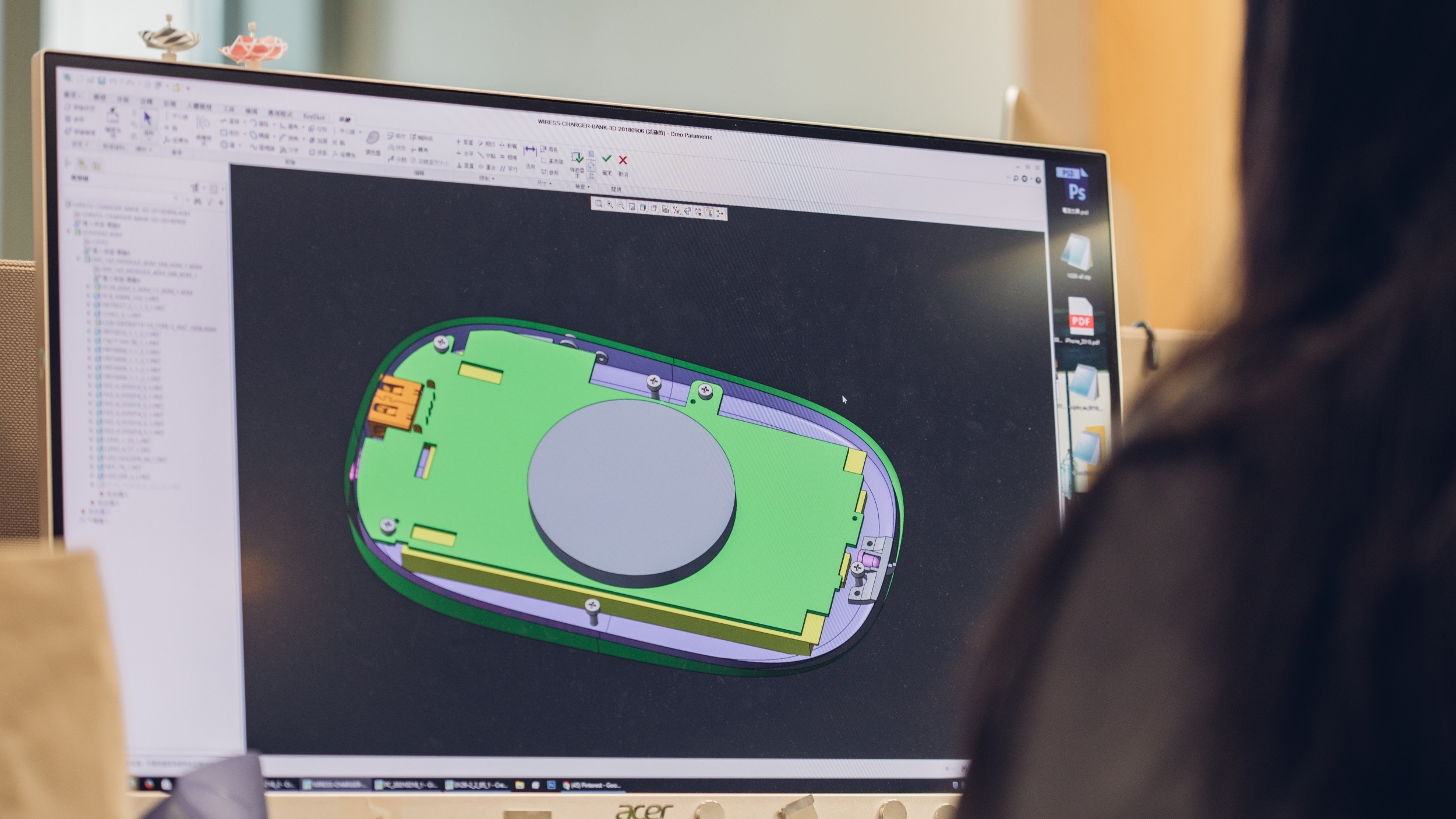 A view from behind of a designer working on a CAD drawing of a Moshi wireless charger