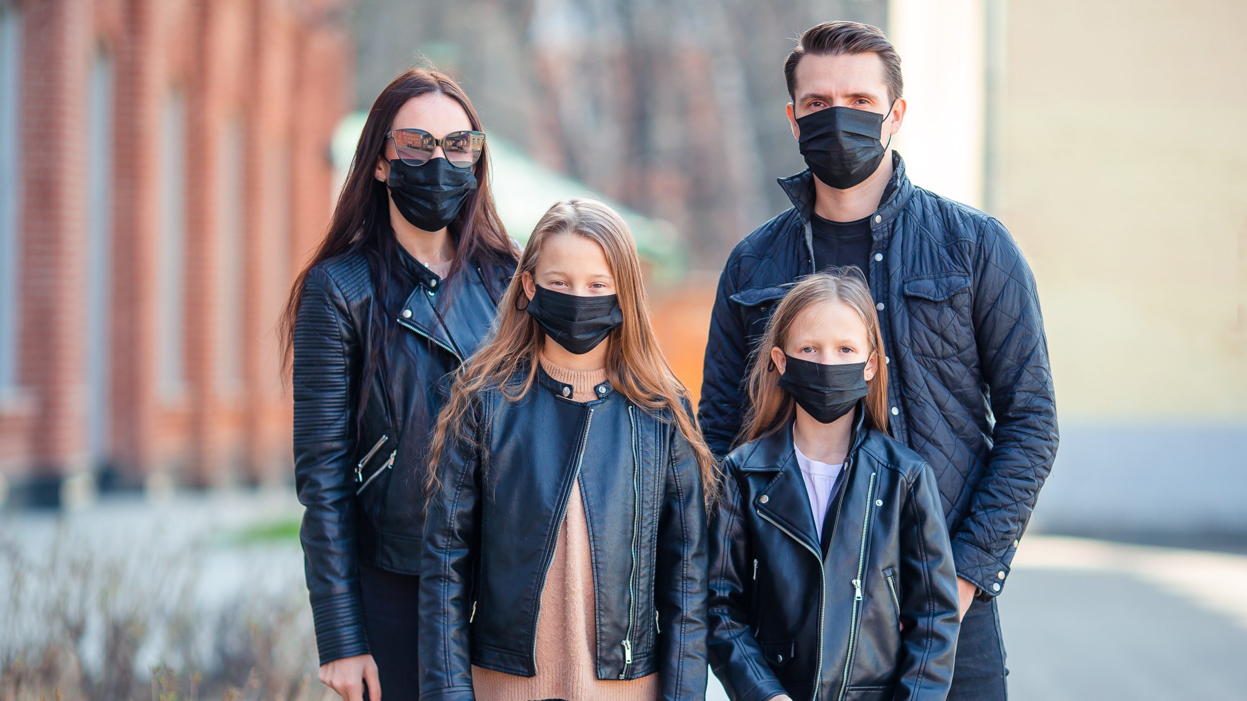 A family standing together outside wearing face masks