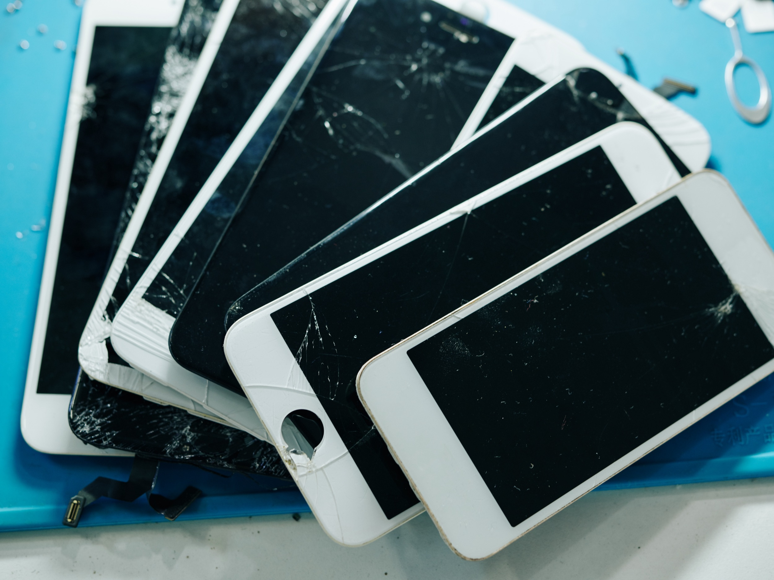 several smartphones with broken or cracked screens