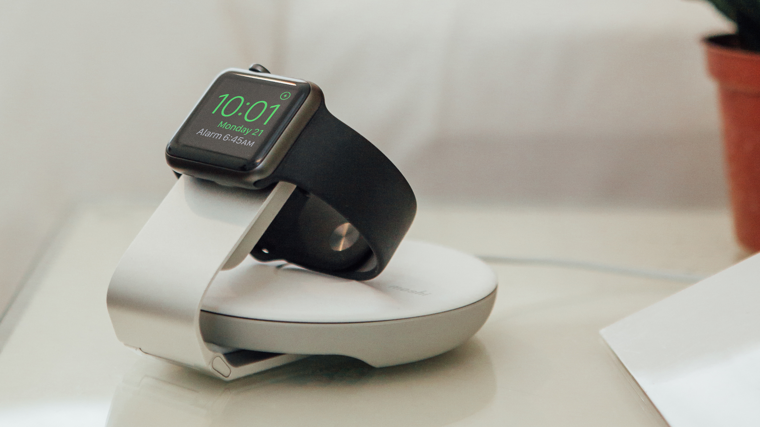 An Apple Watch charging in Nightstand Mode on a Moshi charging stand