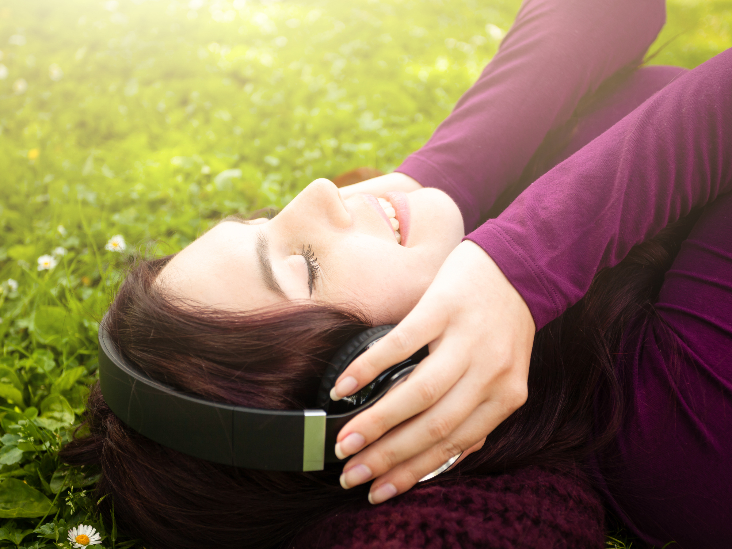 A woman lying on the grass wearing over-ear headphones