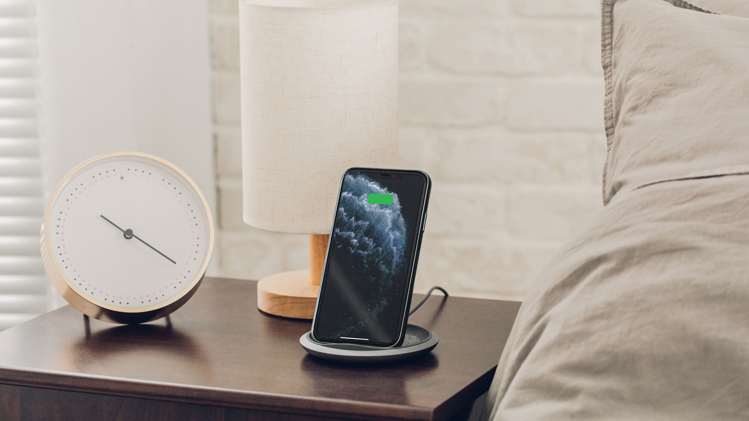 A smartphone on a Moshi Lounge Q charging stand on a bedside table next to a bed