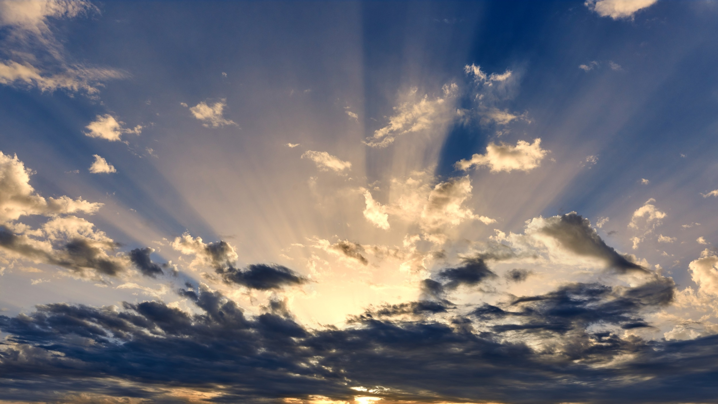 Stock image of a partly cloudy sky with visible sun rays