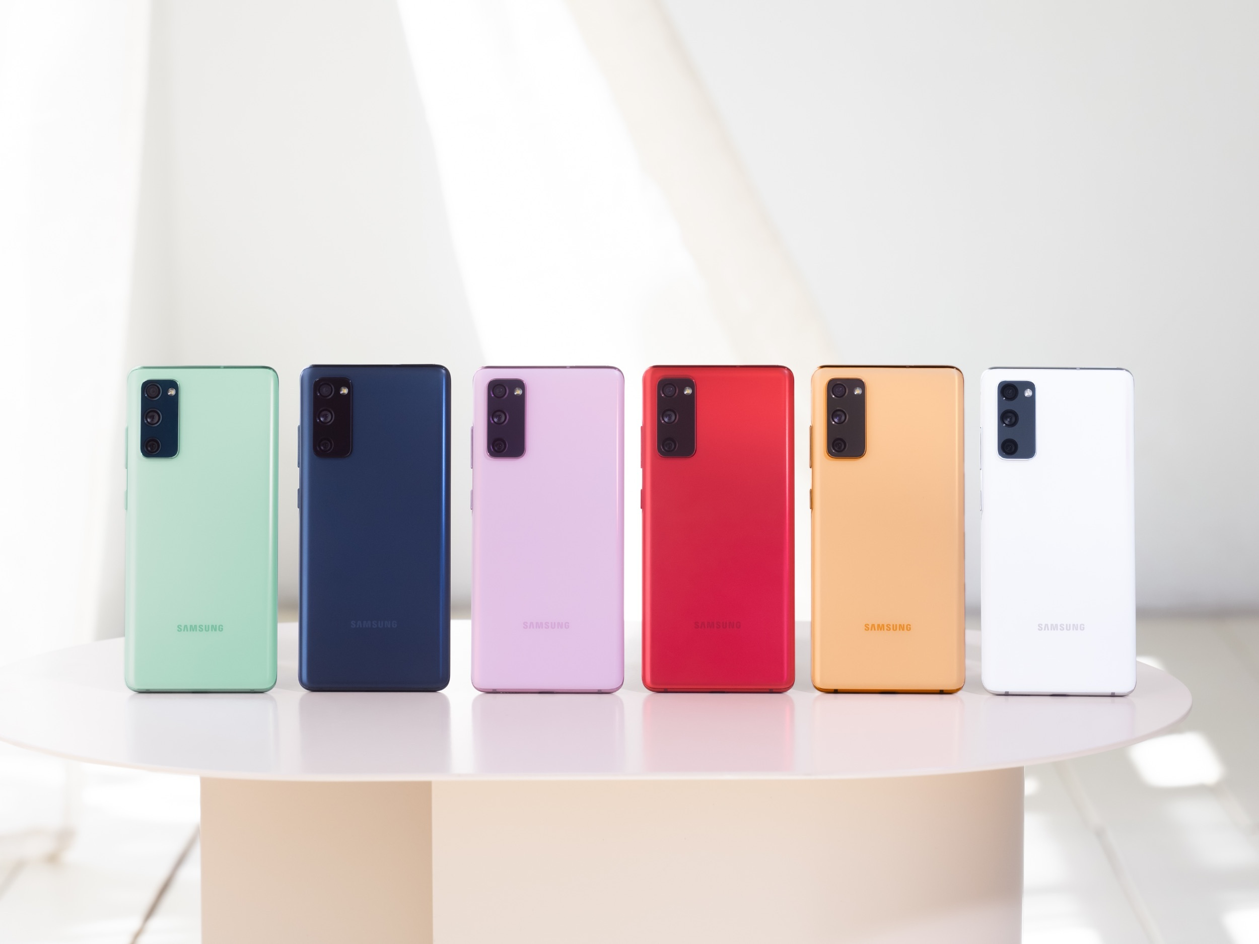 A lineup of Samsung Galaxy S20 FE smartphones standing up on a table