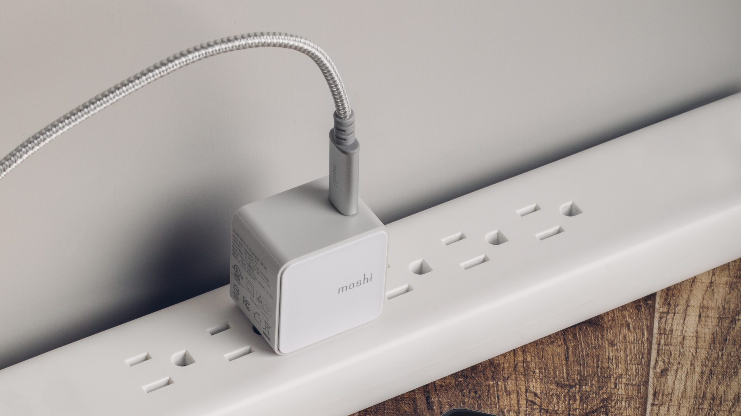 A Moshi Qubit charger connected to a power strip charging a Samsung Galaxy smartphone