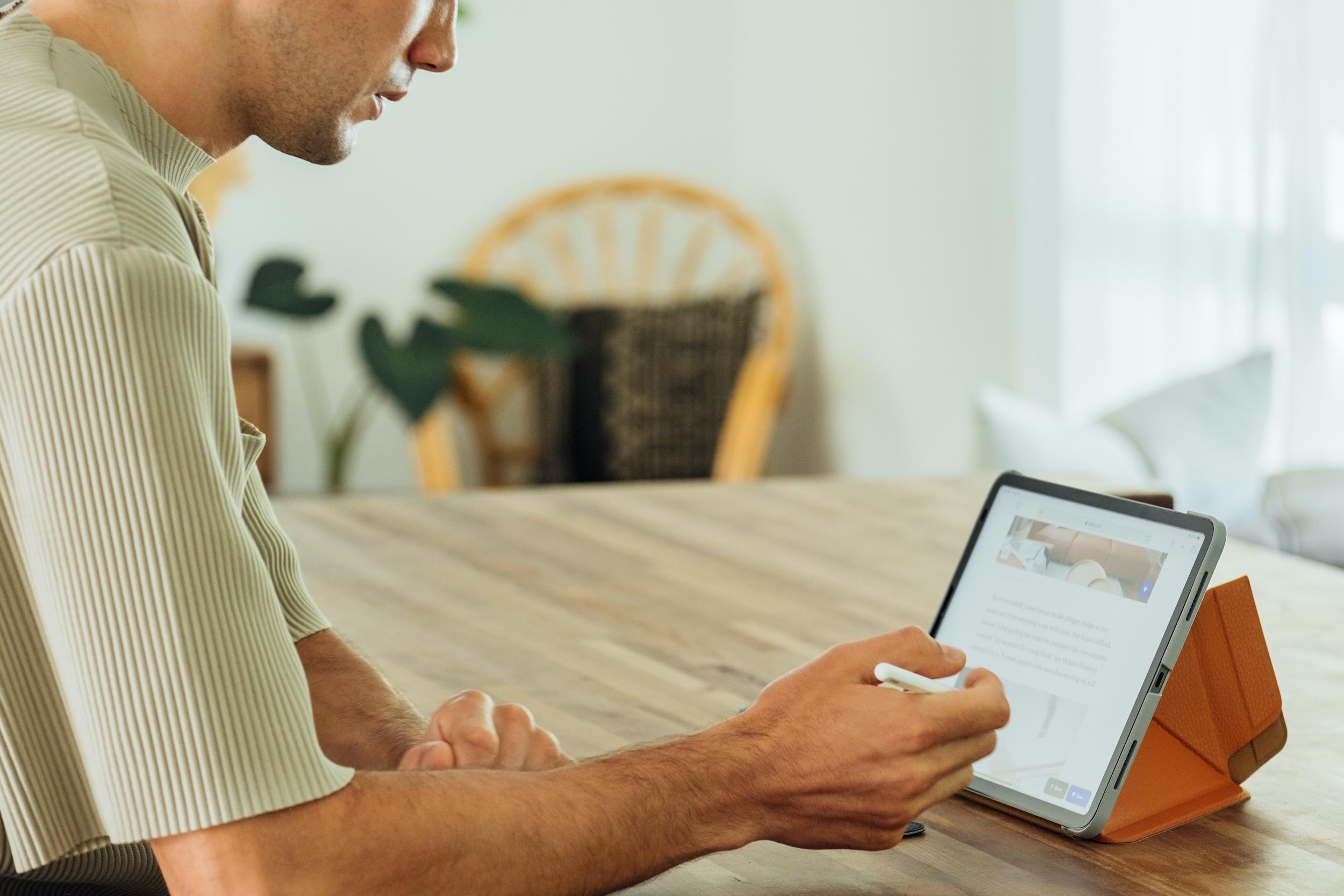 Un homme écrit sur un iPad avec un Apple Pencil sur le comptoir de la cuisine.