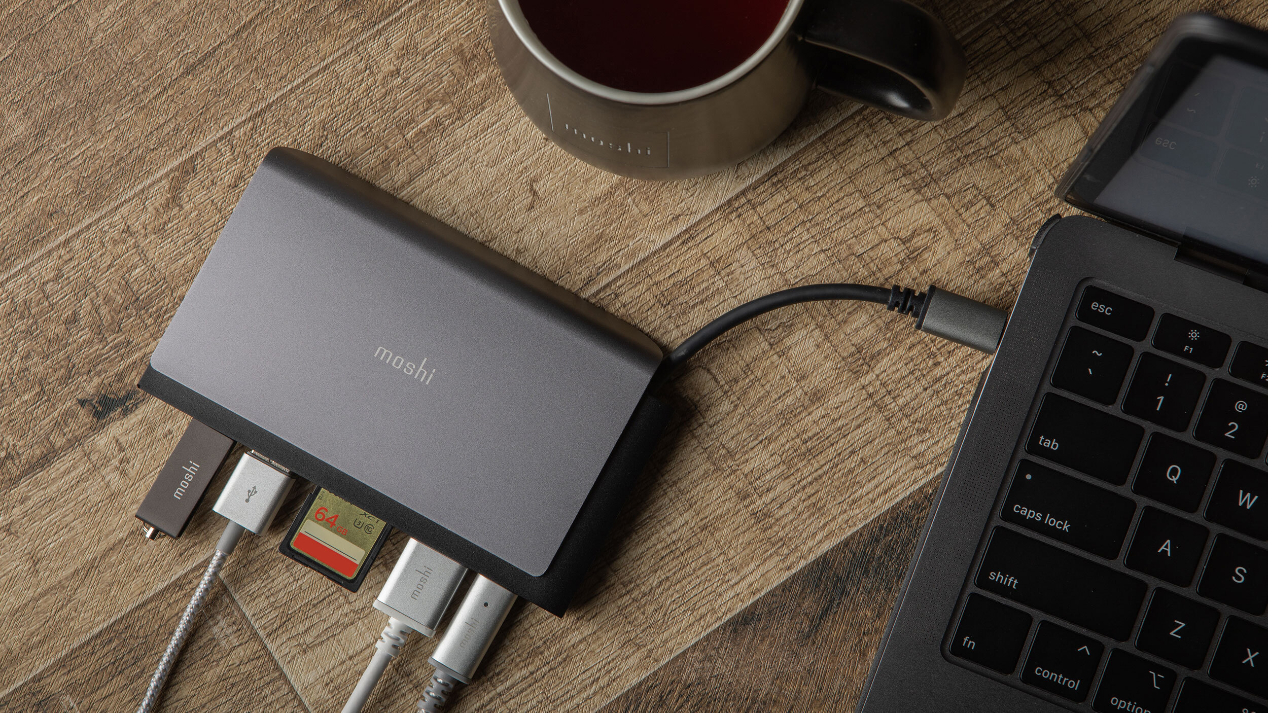 A Moshi Symbus Mini hub connected to a laptop with a USB flash drive, cable, SD card, HDMI cable, and USB-C charger also connected