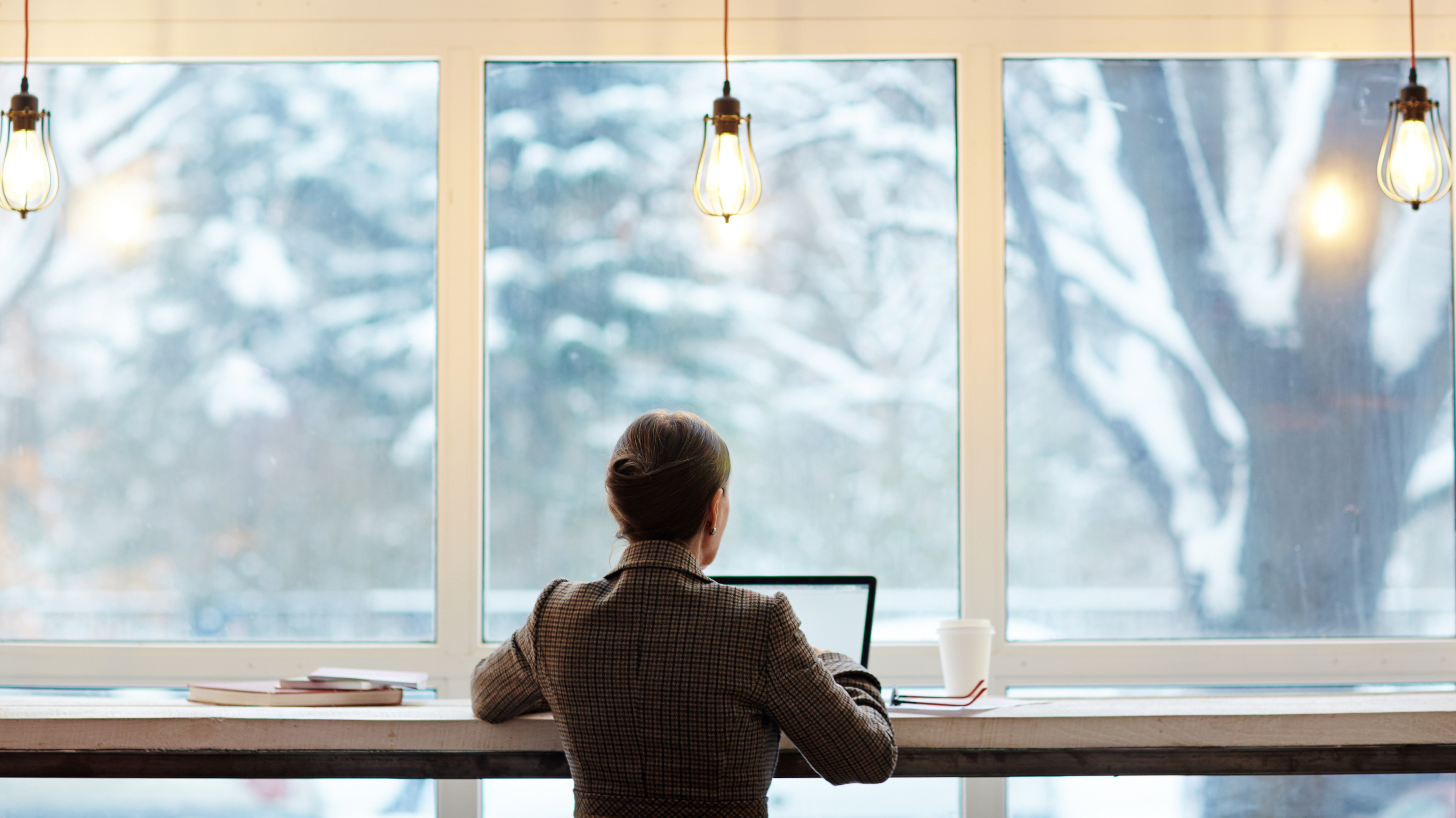 Behind view of a businessperson working at a high table at the window of a cafe