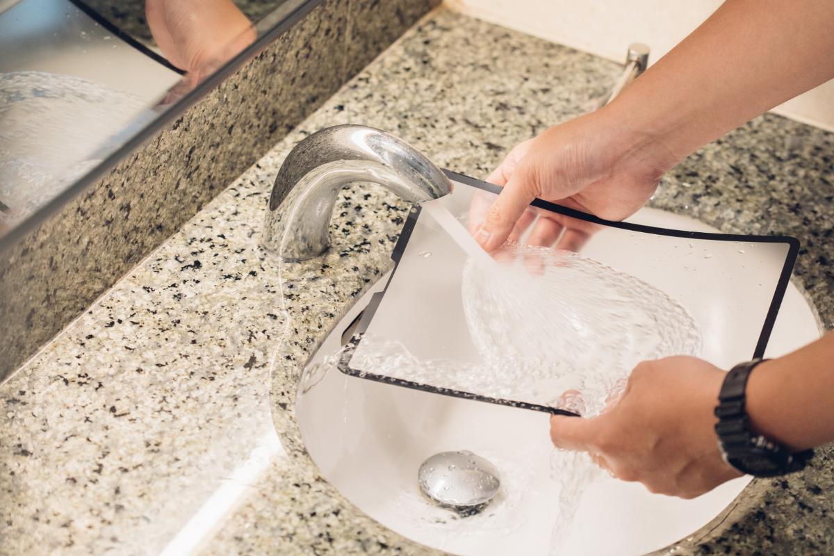 水ですすいで汚れやゴミを取り除きます。 Moshi独自の接着剤は付着物を残すことなく何度も何度もスクリーンに貼り付けれます。