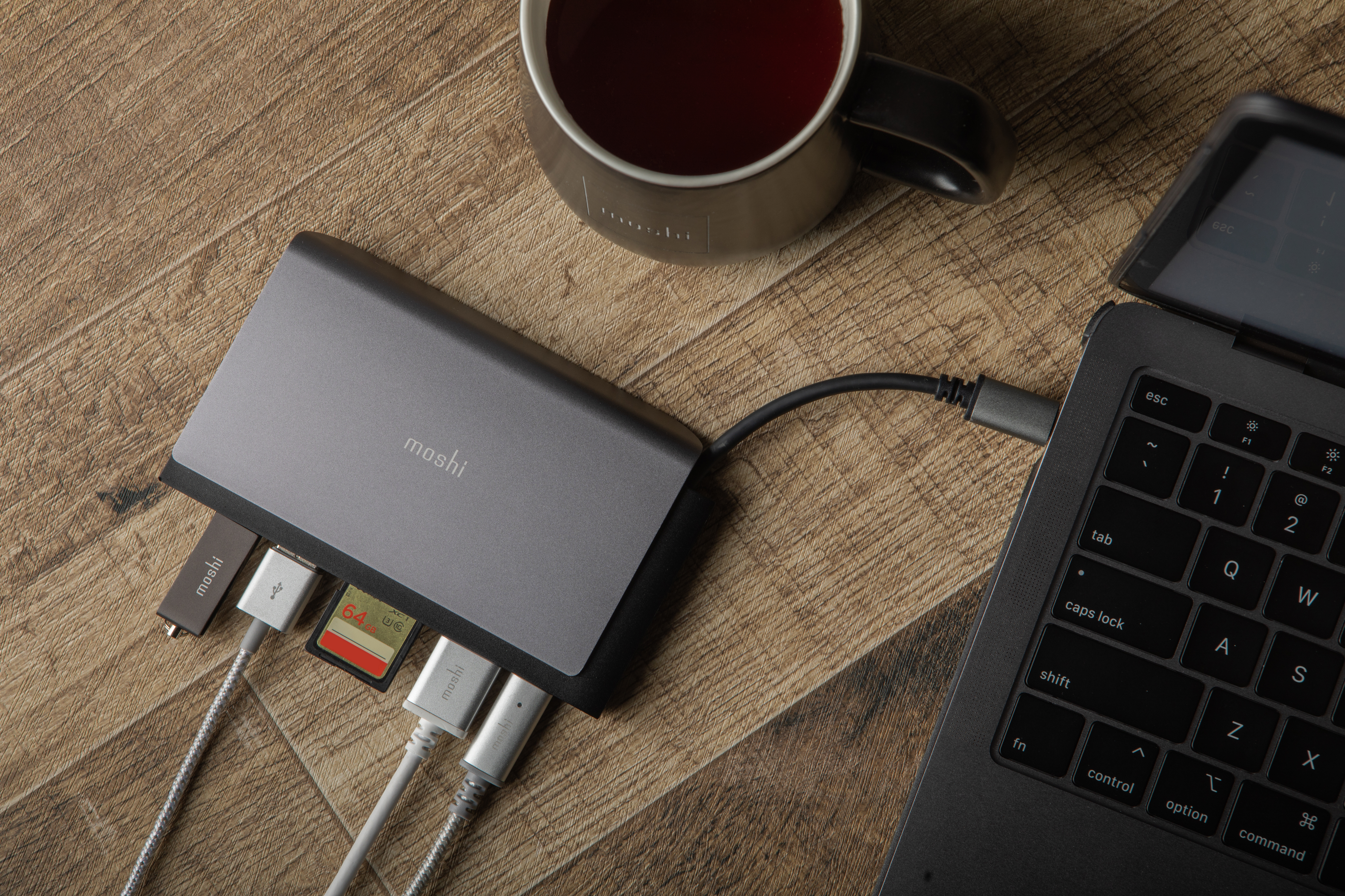 A Moshi Symbus Mini USB-C hub connected to a laptop with various cables and peripherals connected to it