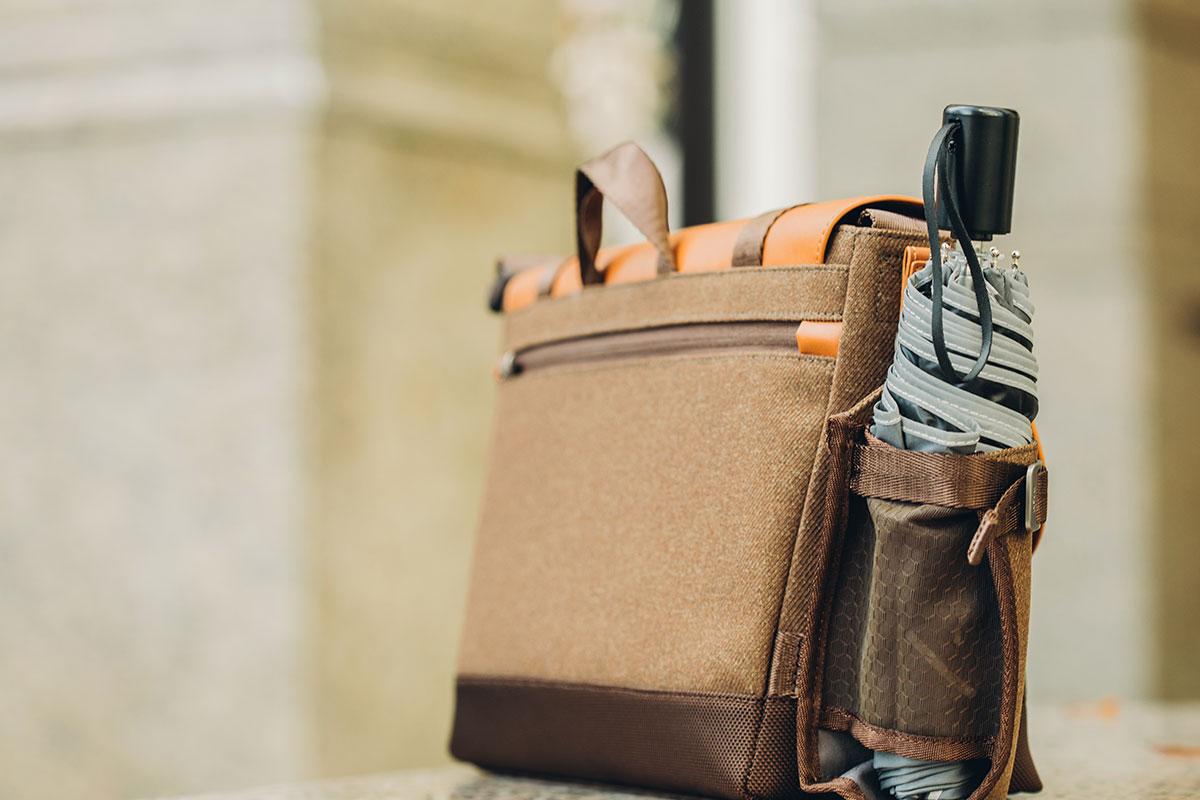 El portabotellas está a mano para colgar el paraguas mojado, separado del contenido del bolso.