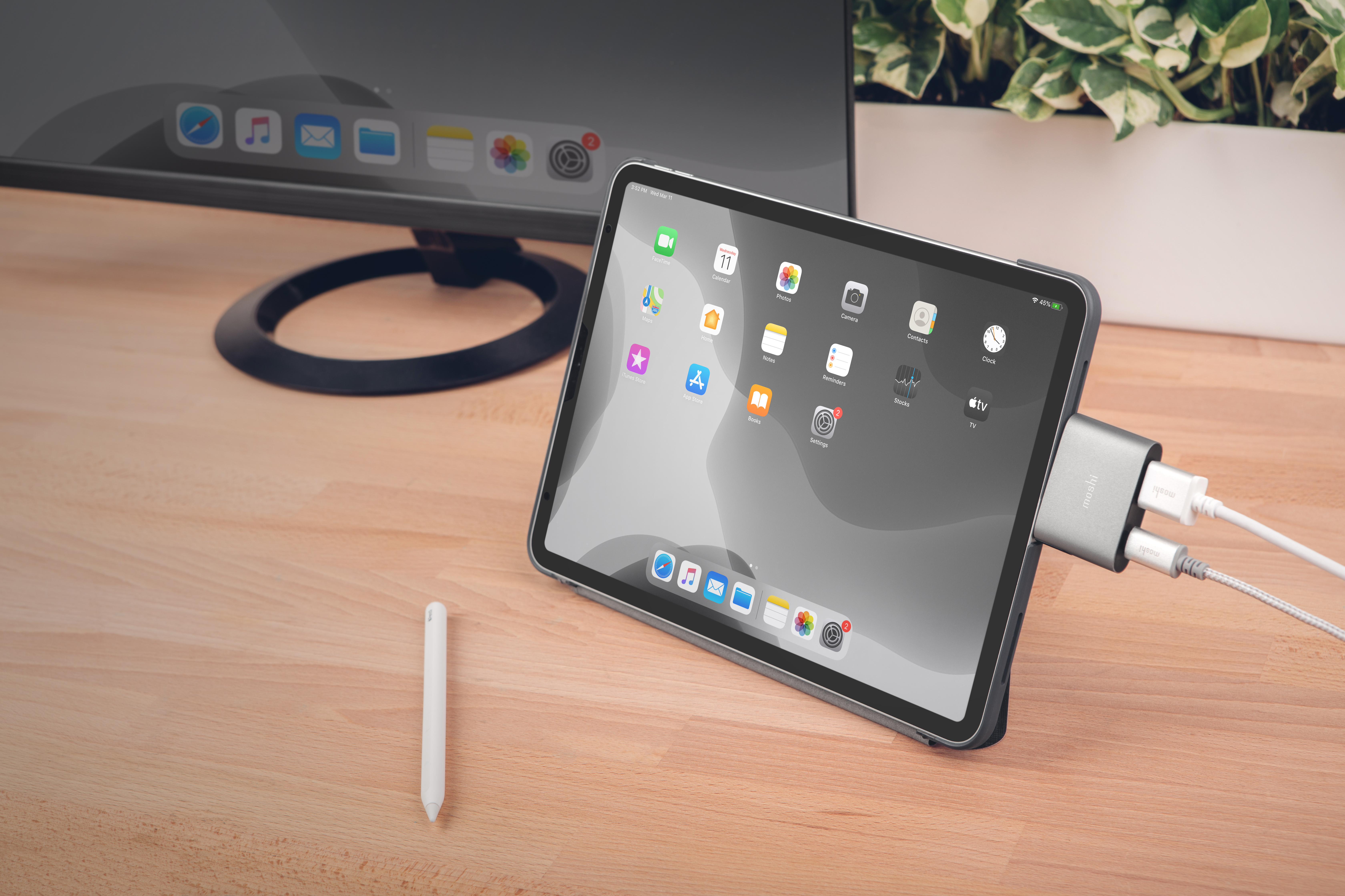 An iPad standing in landscape mode on a desk connected to a Moshi USB-C to HDMI adapter. The display is mirrored on a monitor behind.