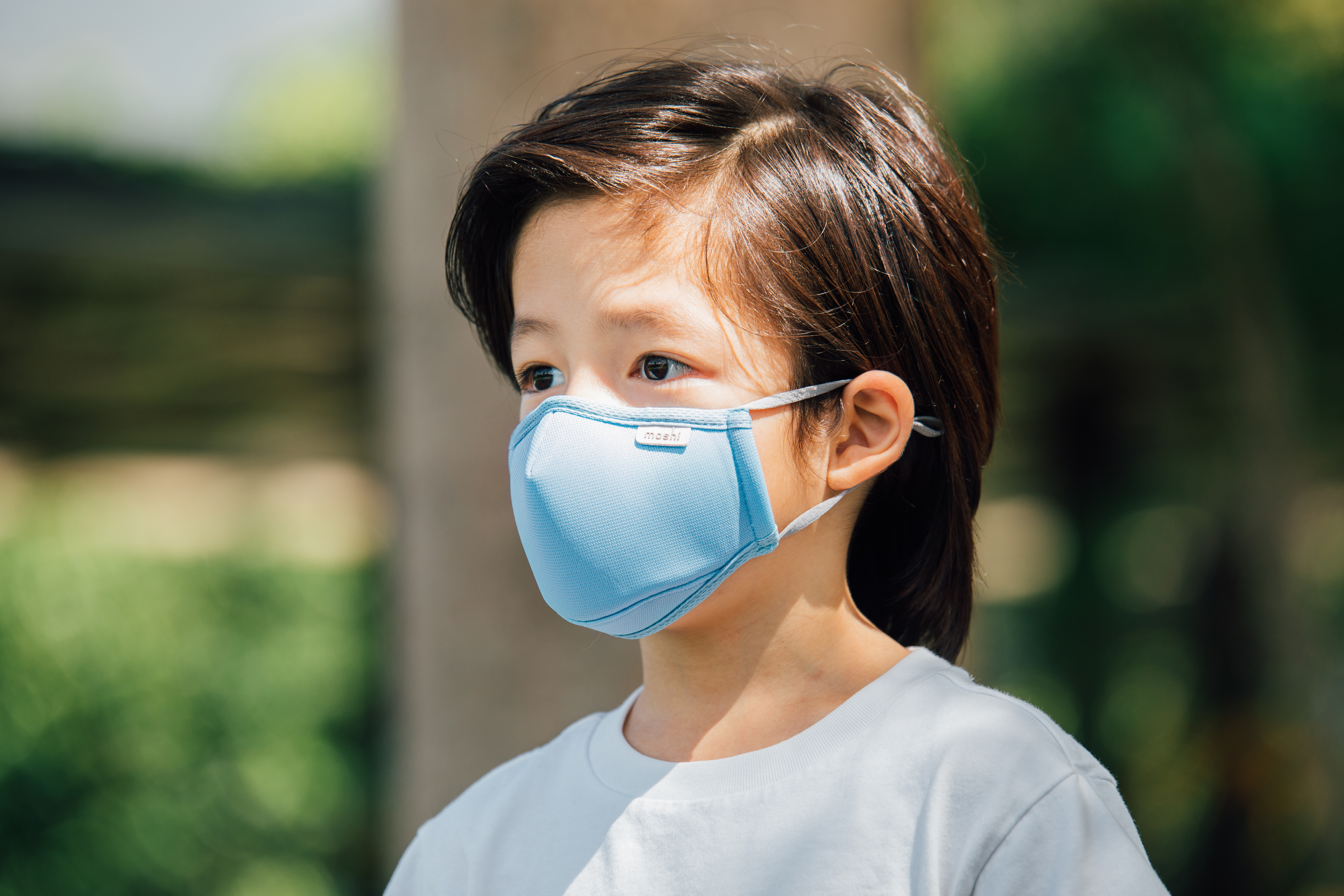 A young boy wearing a Moshi OmniGuard™ mask in a park