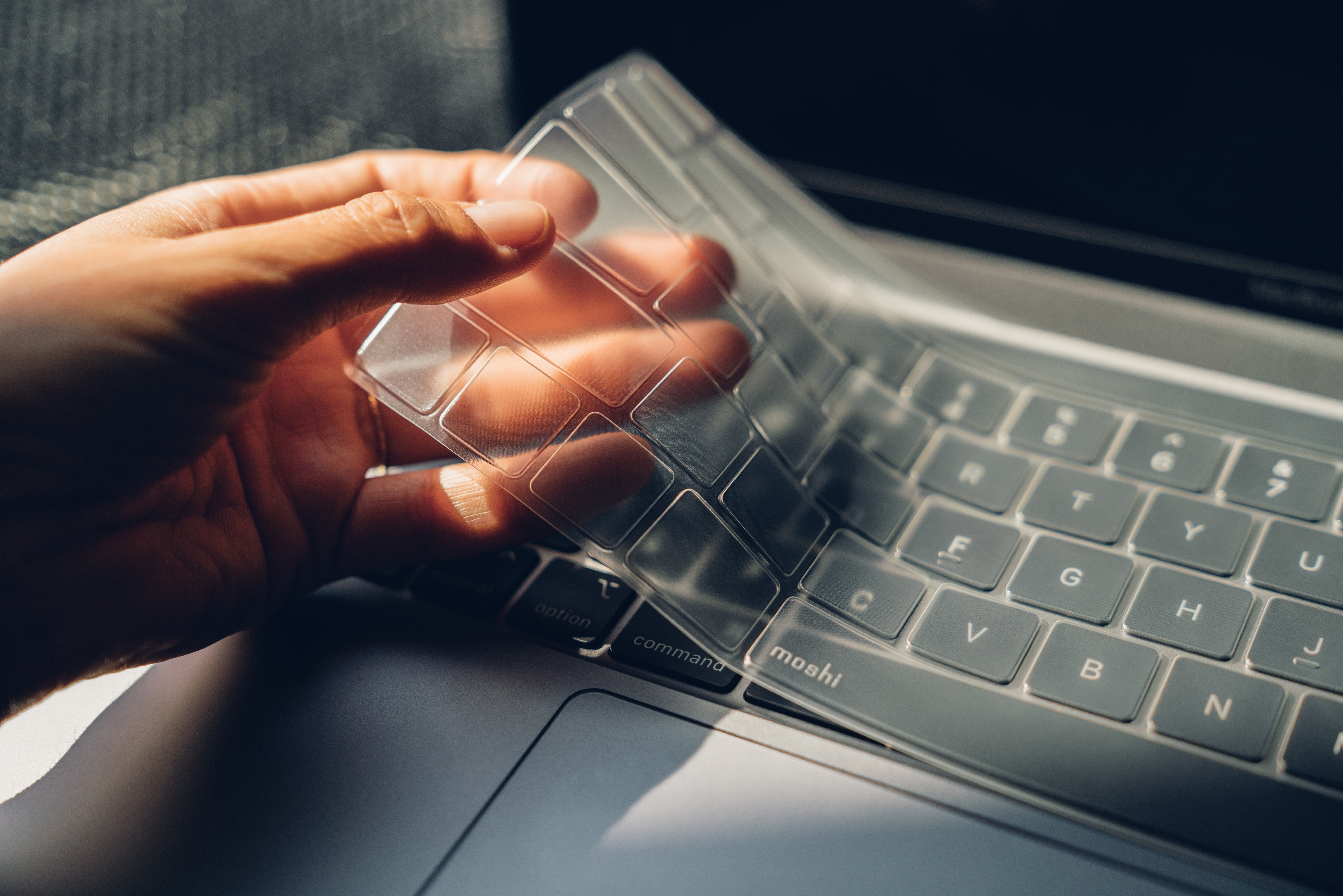 A hand removing a Moshi ClearGuard keyboard protector from a MacBook keyboard