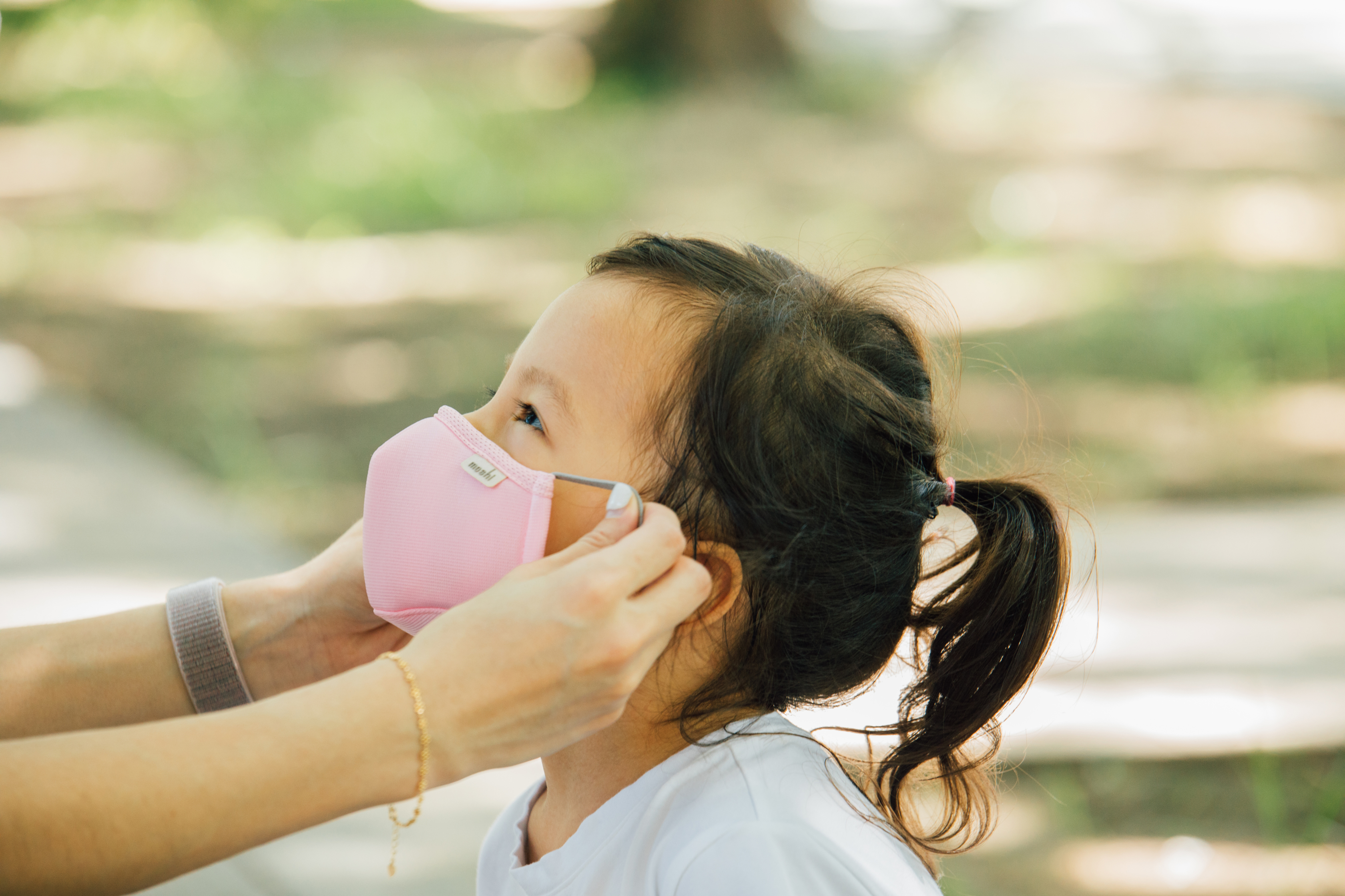 A parent helping their child to fit a Moshi OmniGuard Kids mask in the park