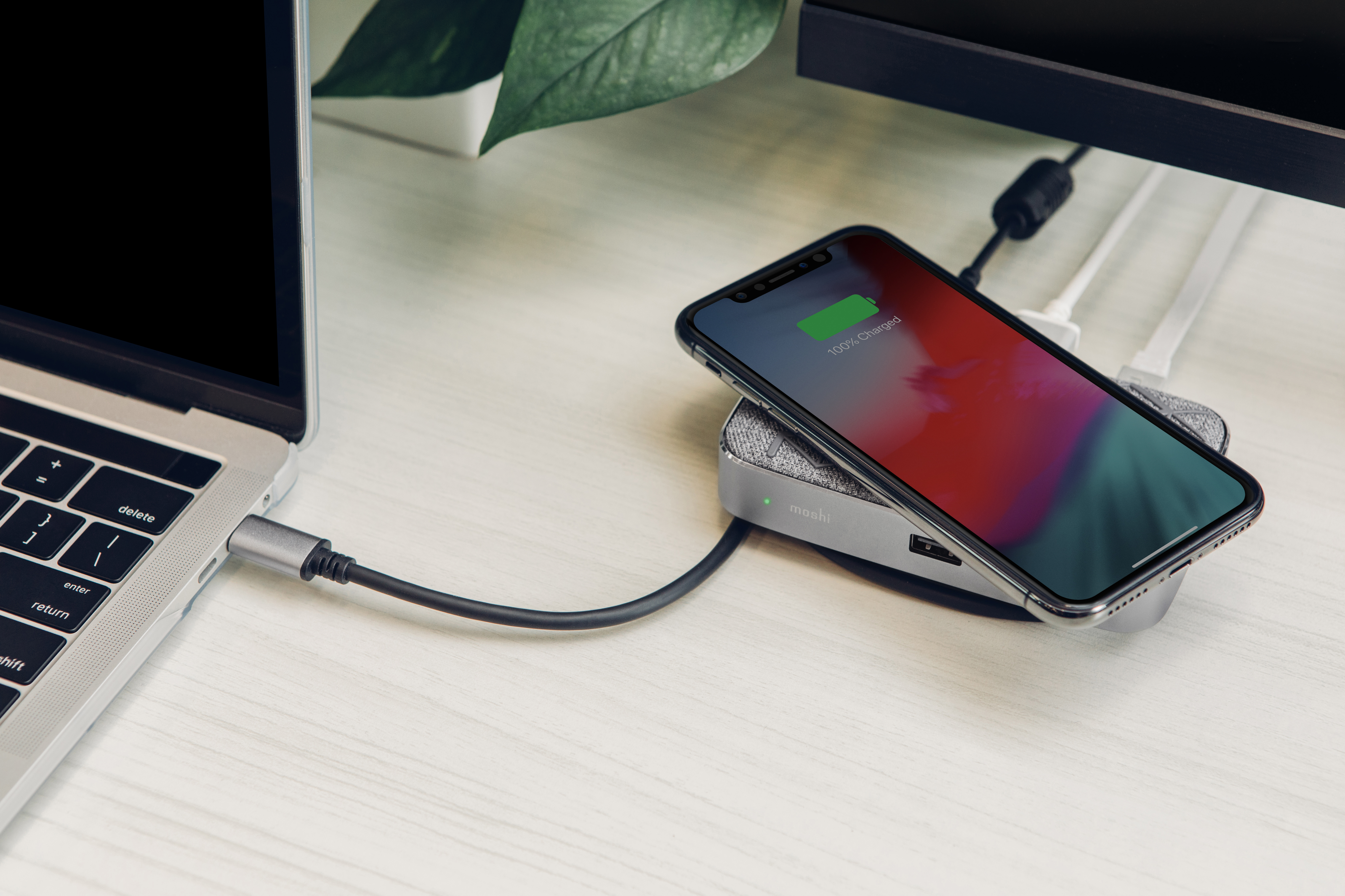 A Moshi Symbus Q hub connected to a MacBook, with an iPhone on top charging wirelessly