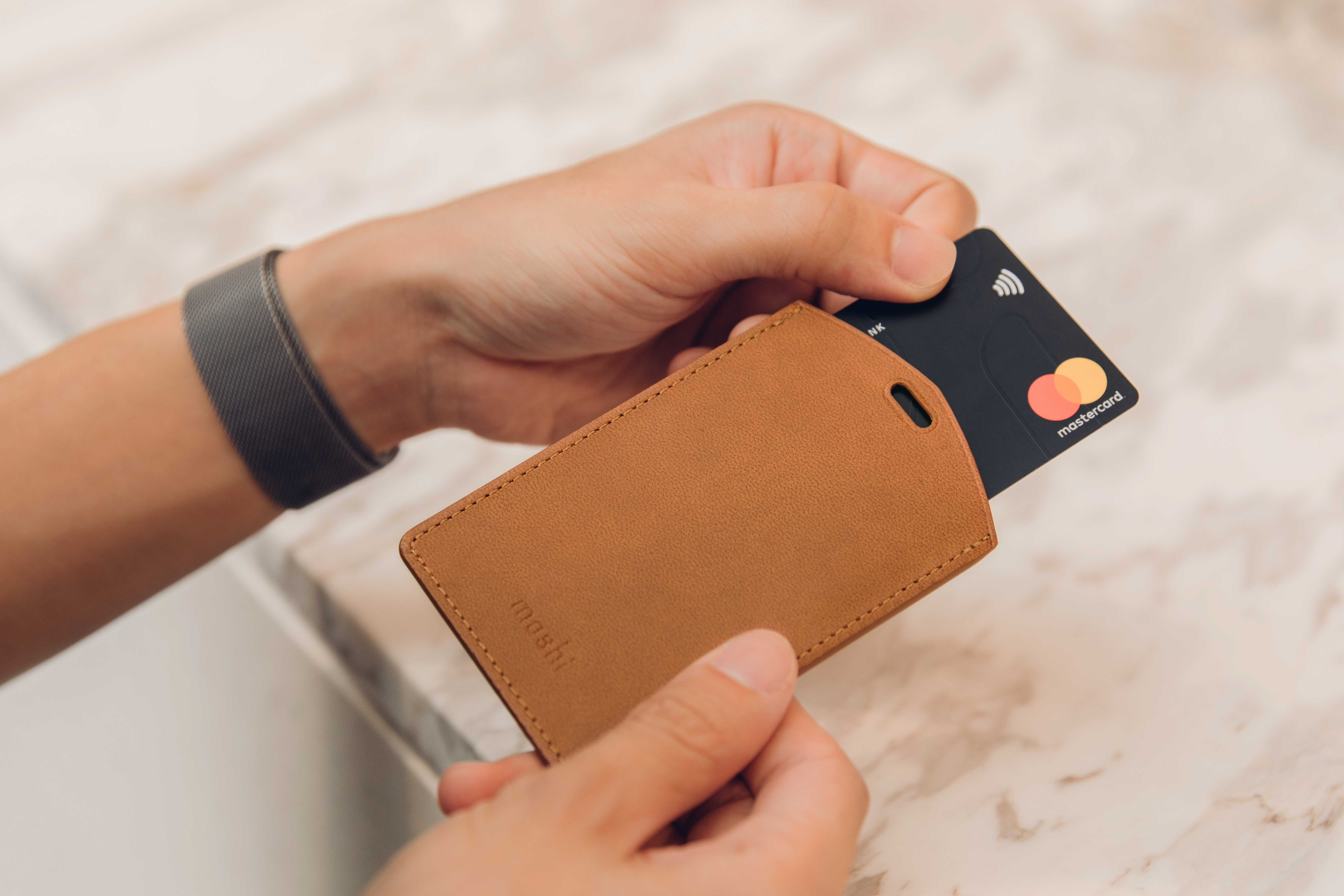 Inserting a credit card into the rear card slot of a Moshi Dual-sided Badge Holder