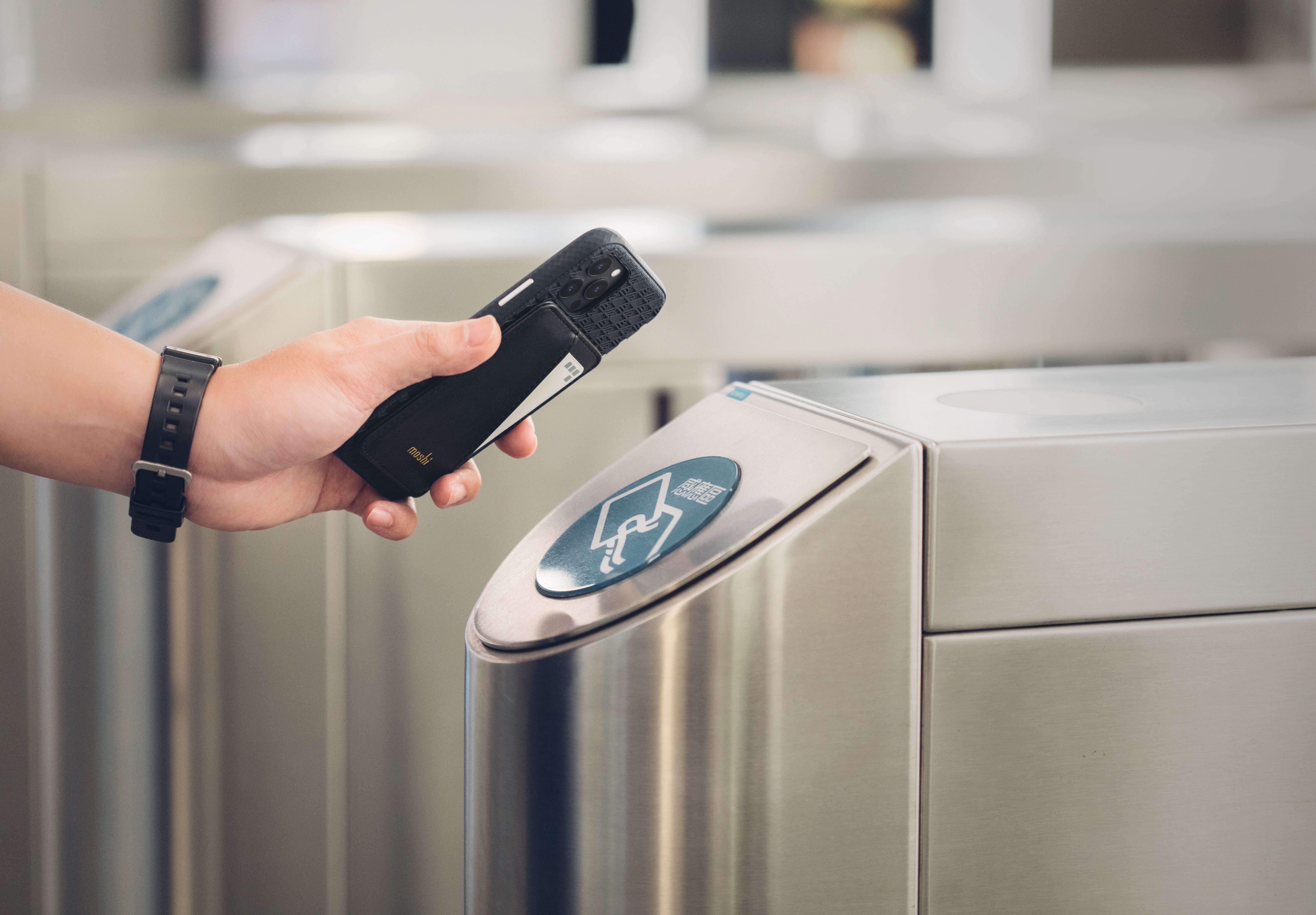 A Moshi SnapTo Slim Wallet attached to a phone and containing and office access card. The card is being scanned on the entry gates at an office