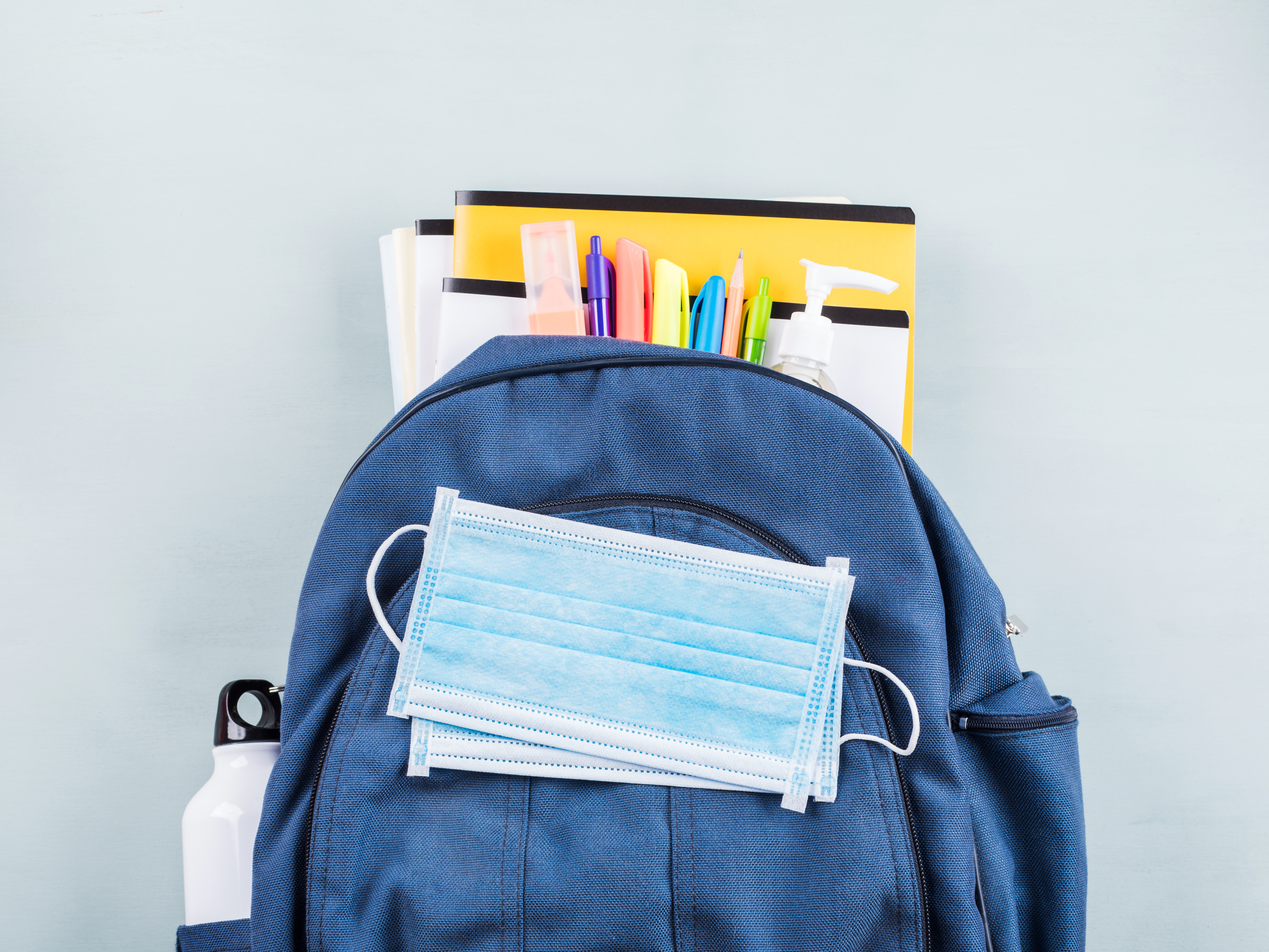 A school backpack with a disposable mask resting on top