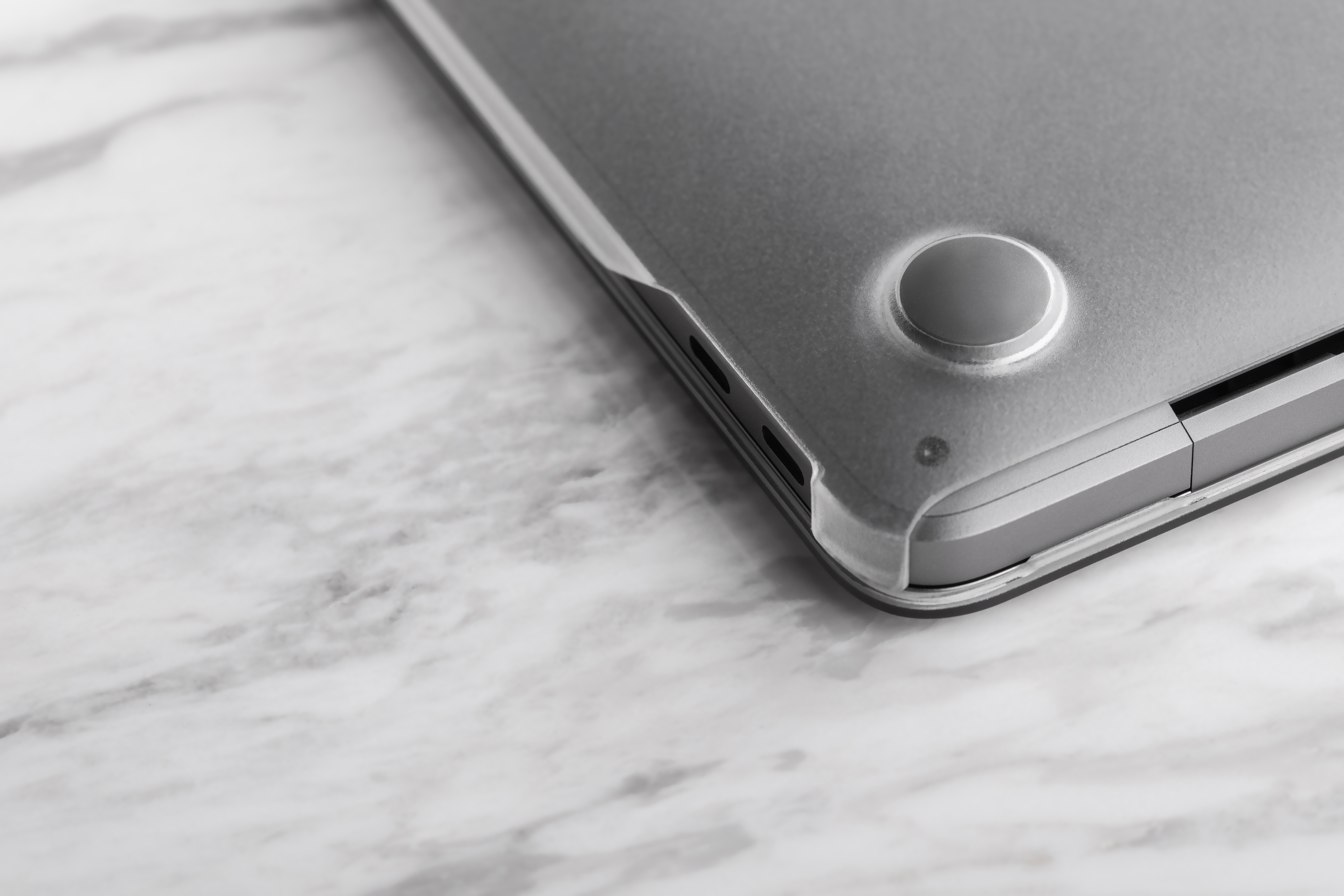 A MacBook bottom-up on a table with a Moshi iGlaze shell case installed