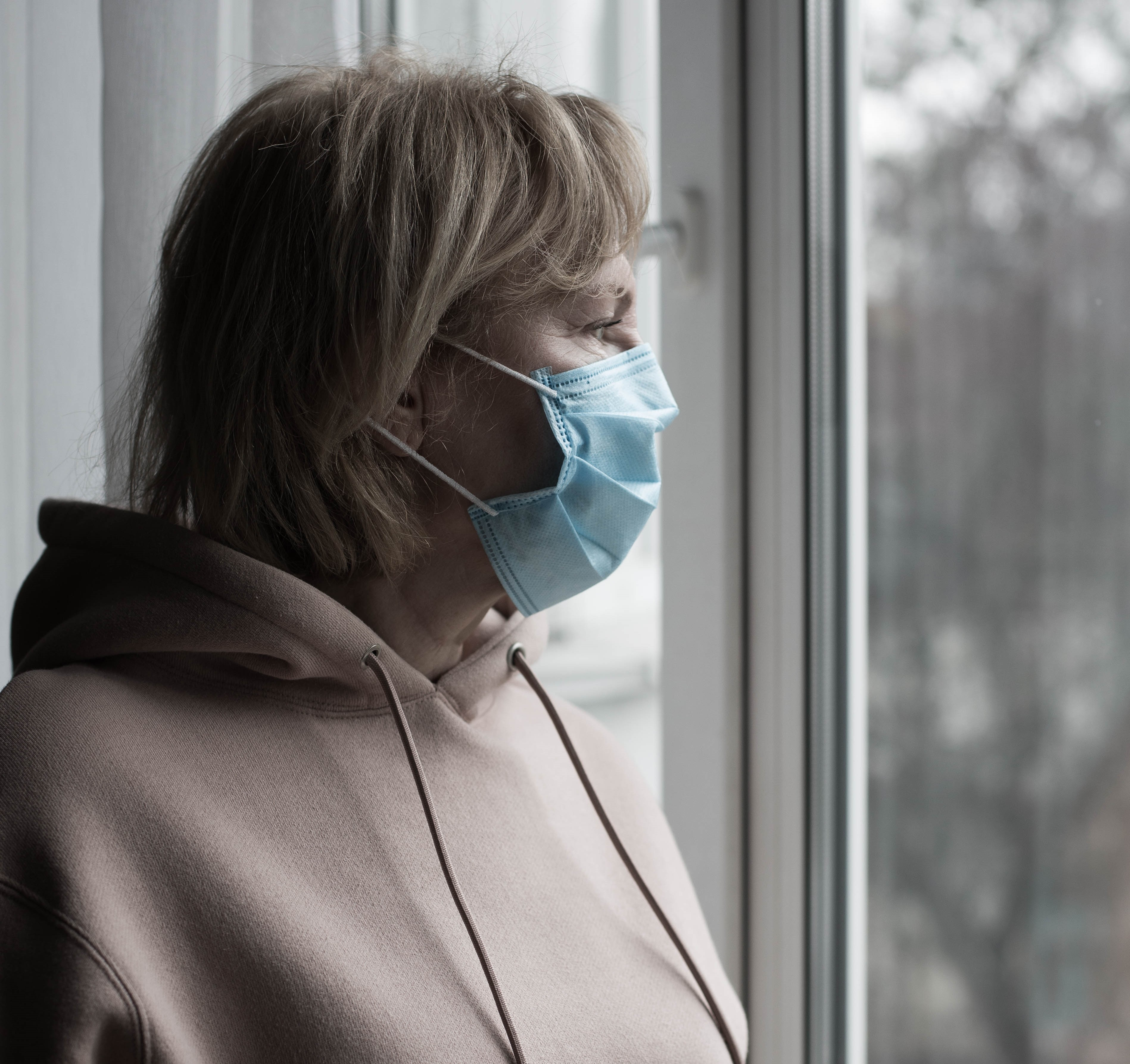 A woman wearing a surgical mask which does not seal around the edges