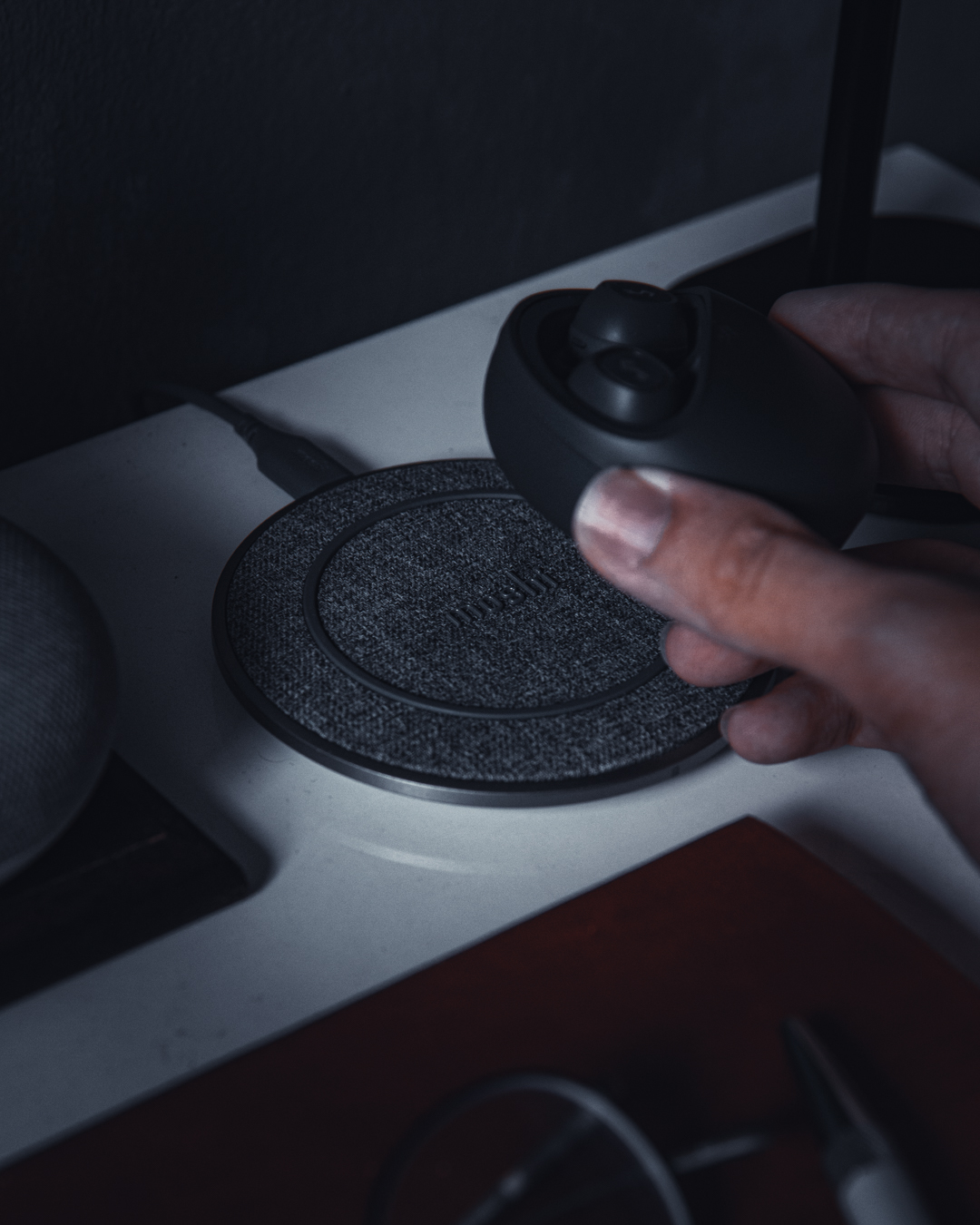 A hand placing a set of true wireless earbuds on a Moshi Otto Q wireless charger