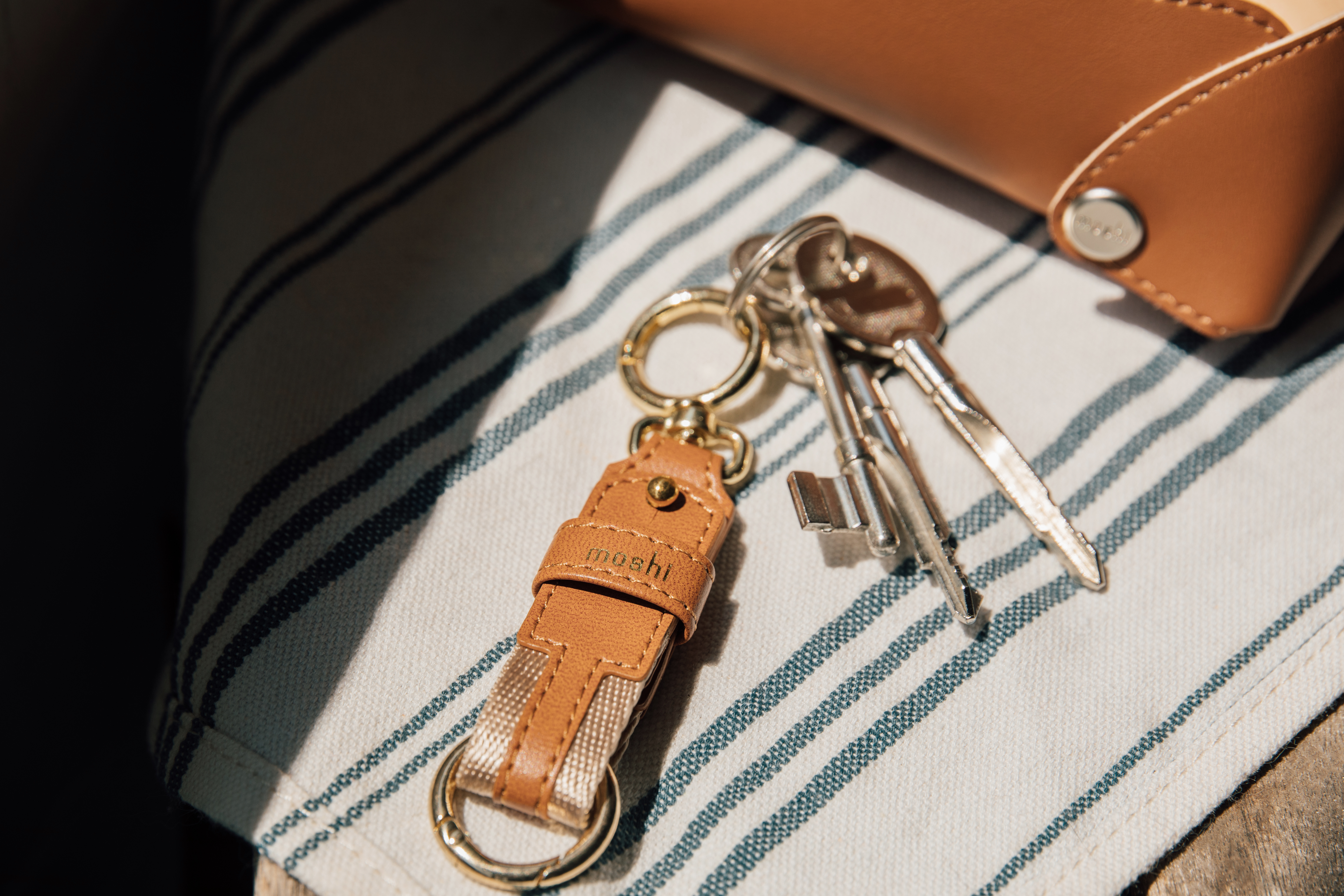 A Moshi key ring on a table with three keys attached