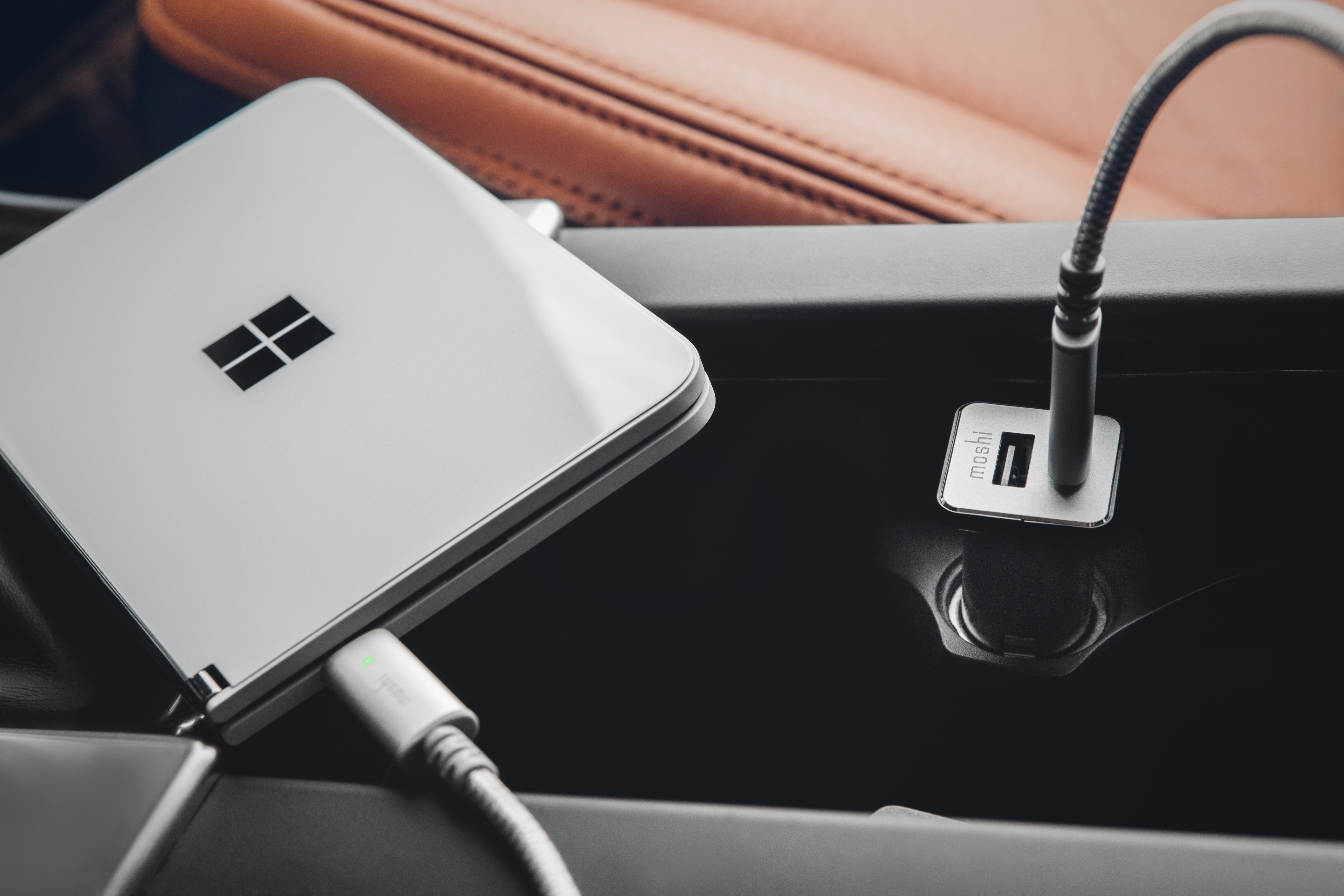 A Moshi QuikDuo car charger charging a Surface Duo in a car center console