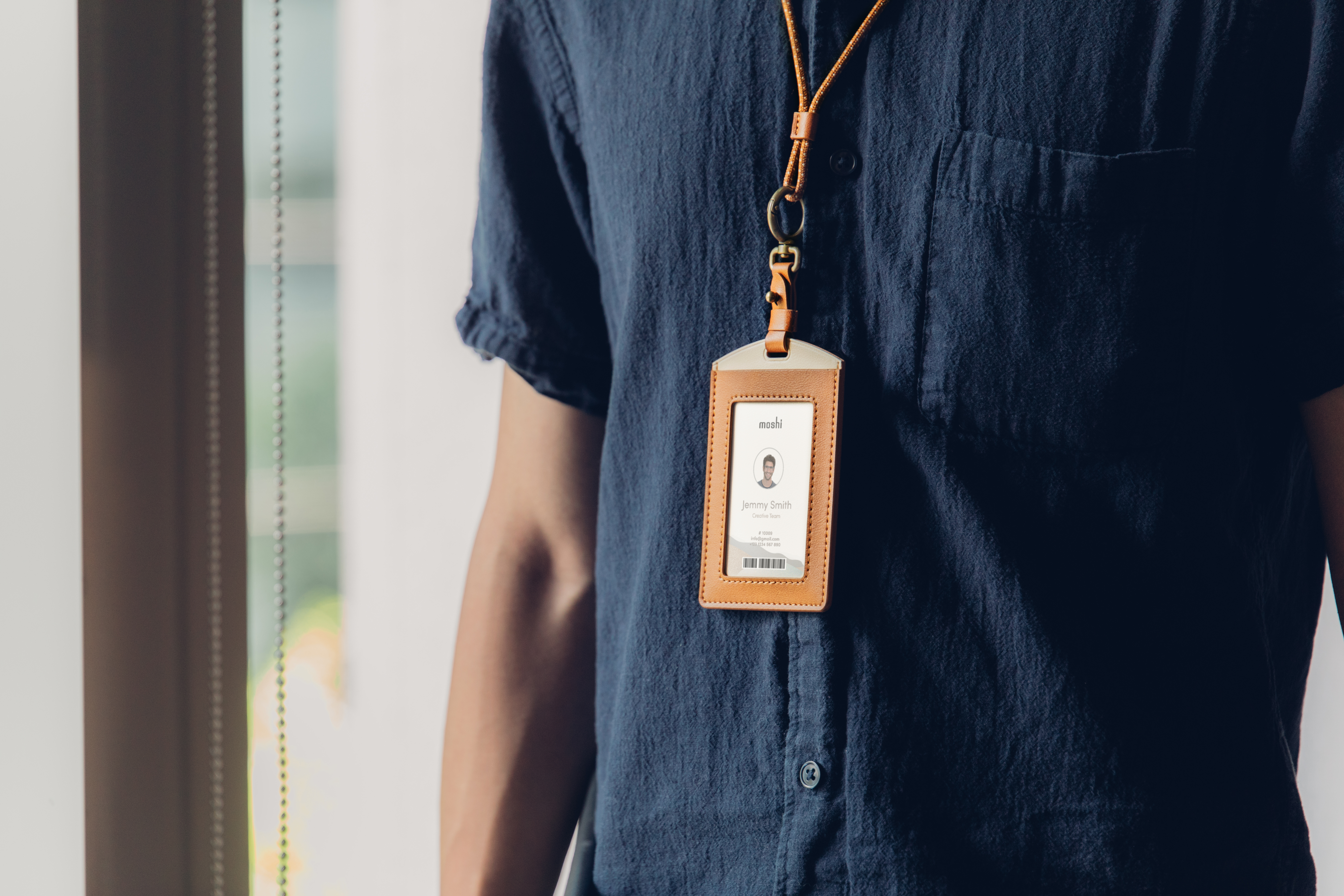 An office worker with a Moshi Dual-sided badge holder around their neck, office ID is visible in the holder